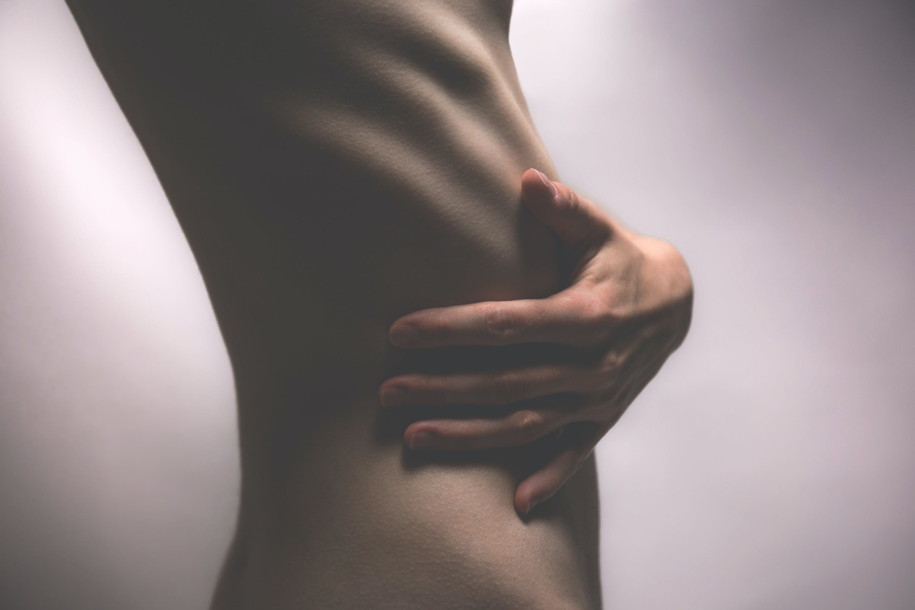 Side View Photo of Person Touching Stomach