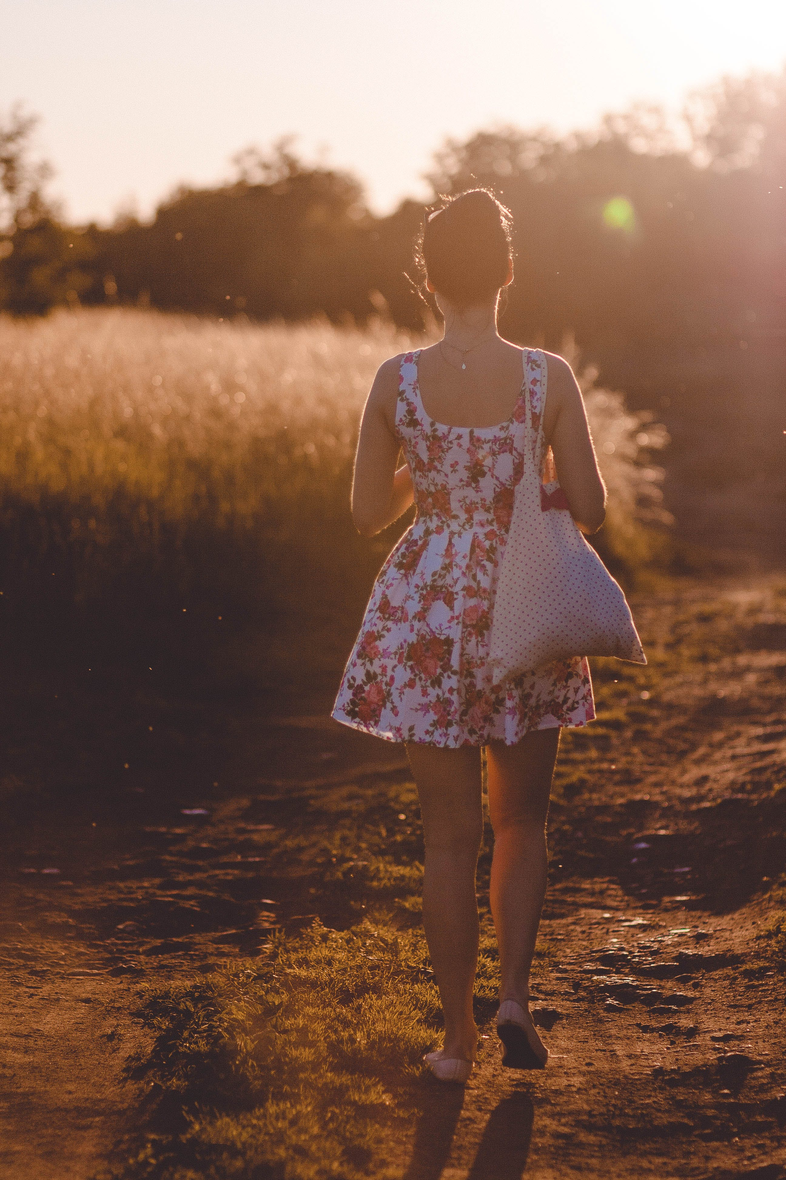 Woman in White and Pink Floral Sleeveless Dress Walking on Brown Road during Sunlight