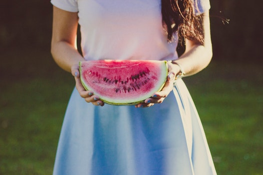 Woman in White and Blue Dress Holding Water Melon