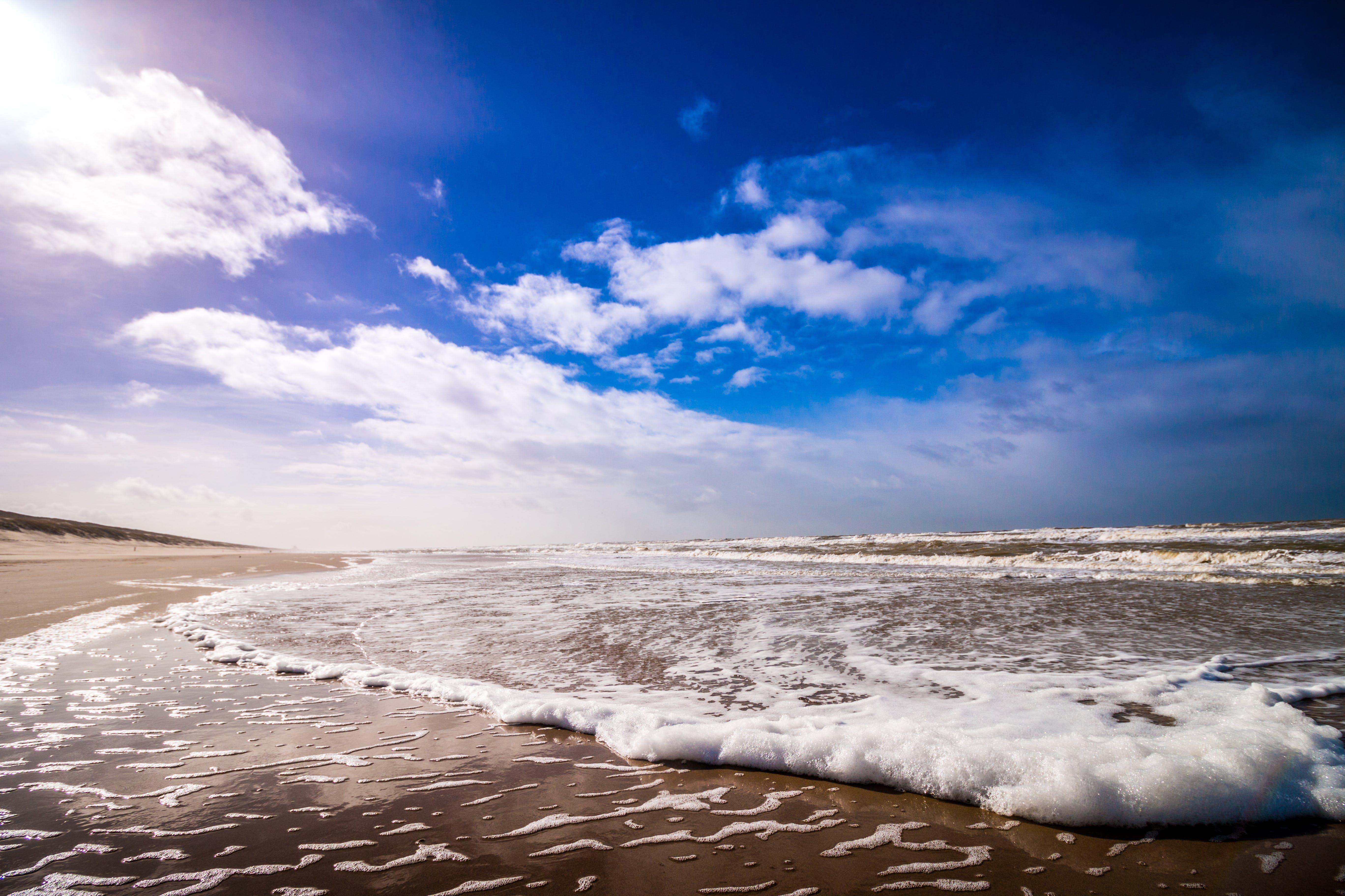Bike Waves of Sea Under Clouded Blue Sky during Daytime