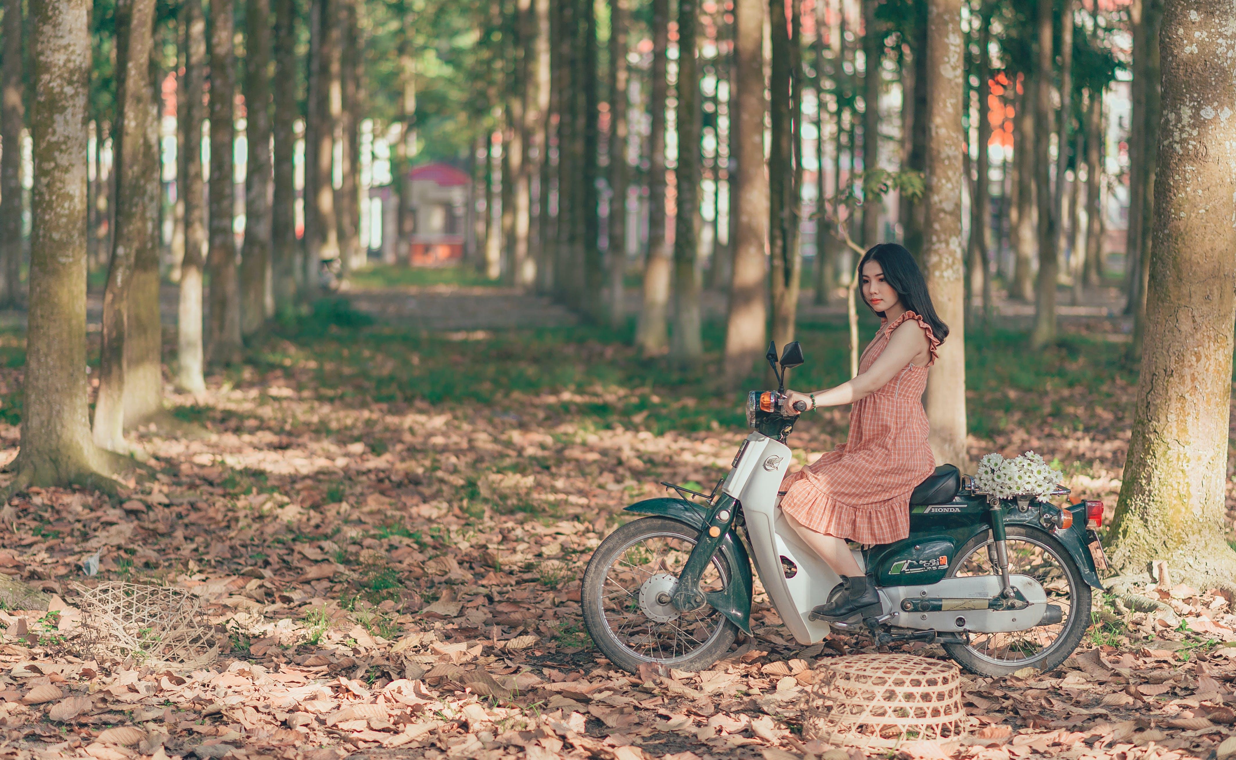 Woman Riding Underbone Motorcycle Between Trees