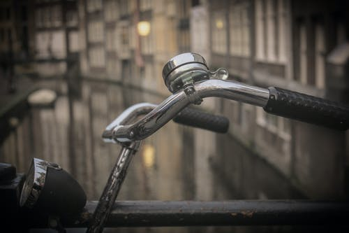 Black and Gray Bicycle Handle Bar With Bell Near Canal
