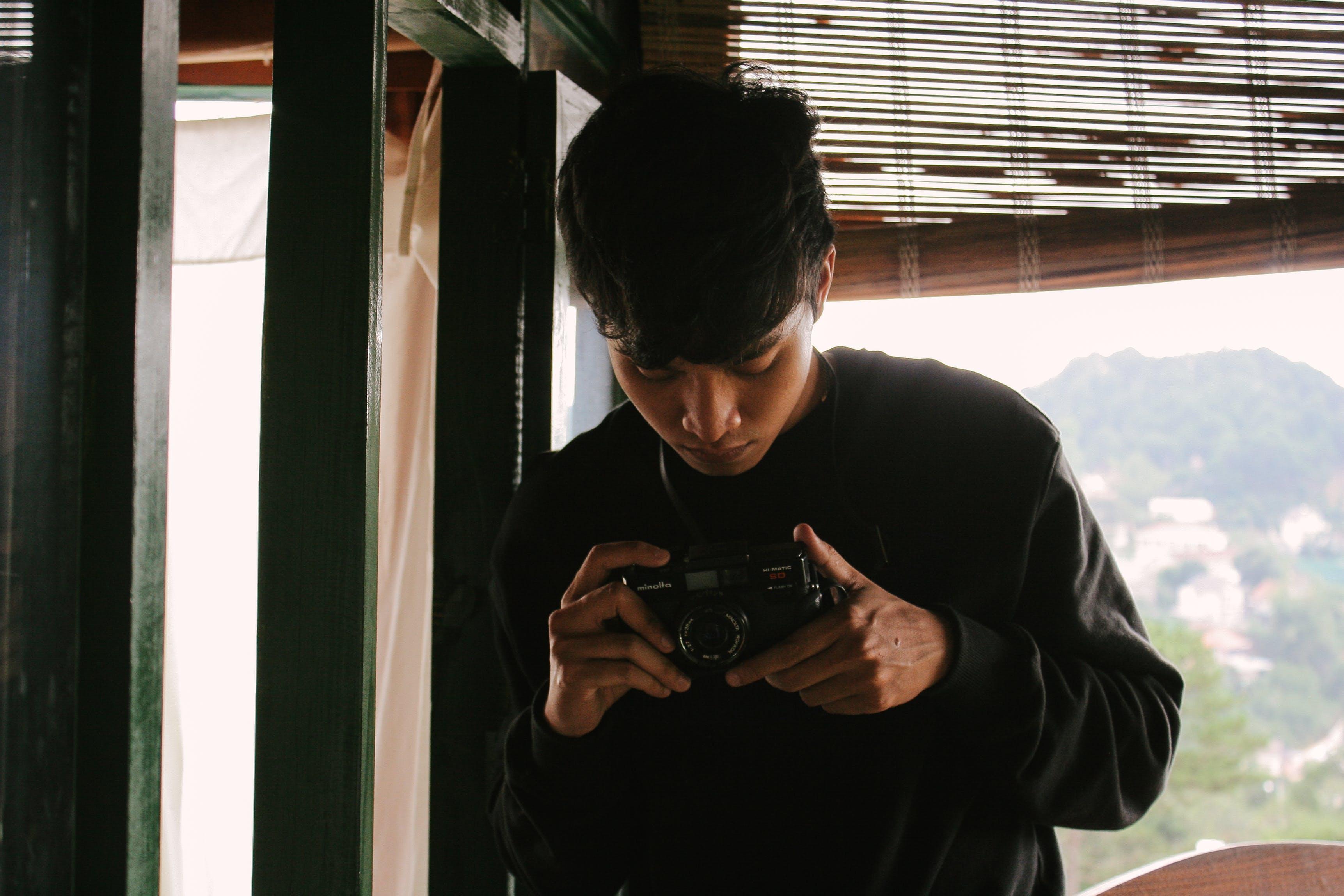 Close-Up Photo of Man Holding Vintage Camera