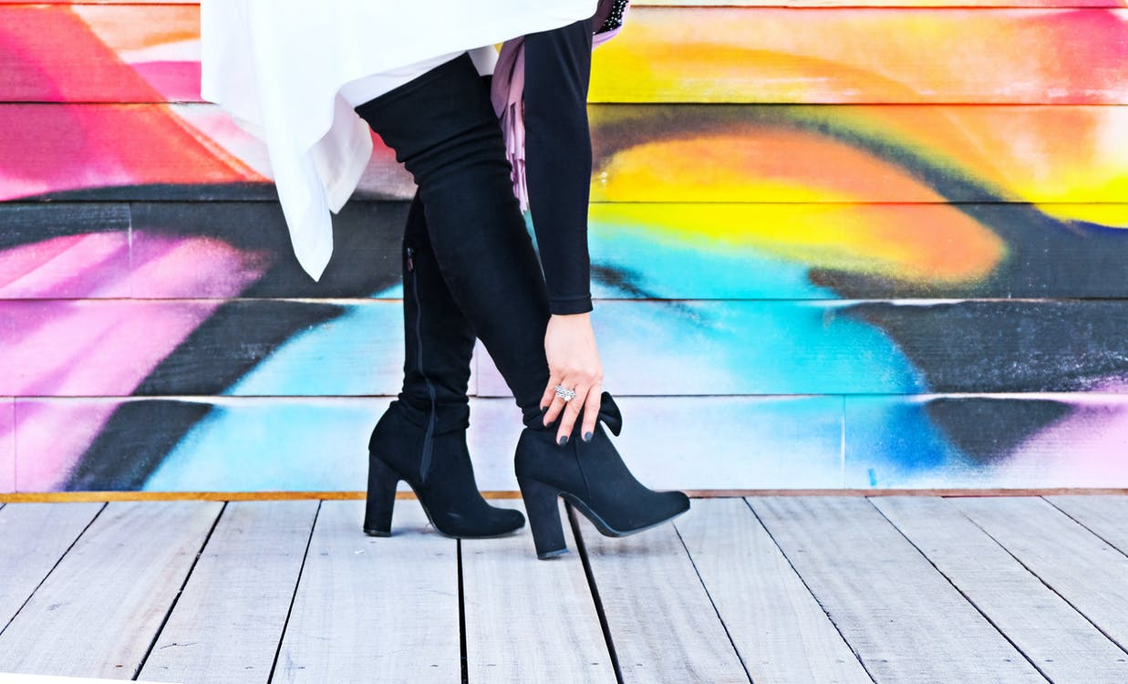 Photo of Woman Touching Right Heeled Shoe Beside Wall