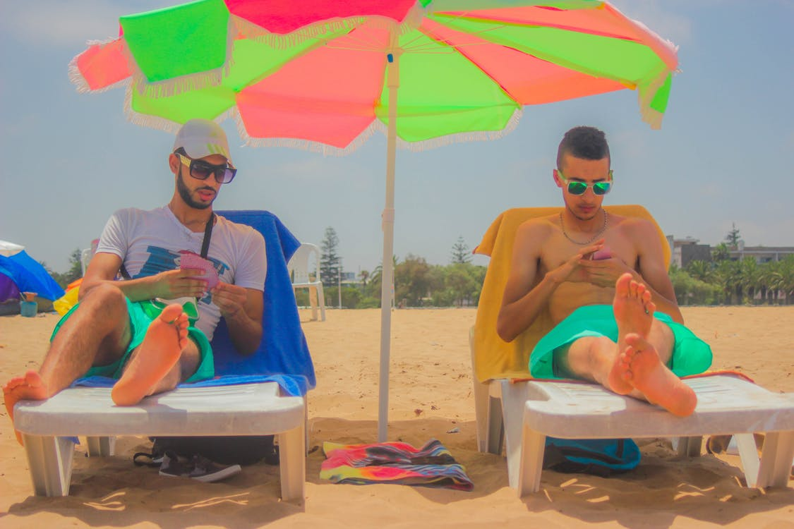 2 Man Sitting on White Beach Lounger With Green and Pink Patio Umbrella in Between