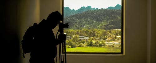 Silhouette of Man Standing Near Window While Holding Camera With Tripod