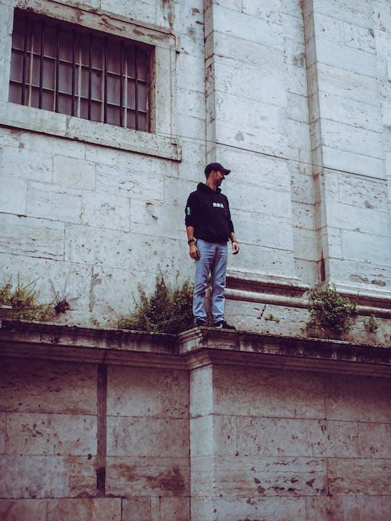 Man in Black Hooded Jacket Standing on Edge
