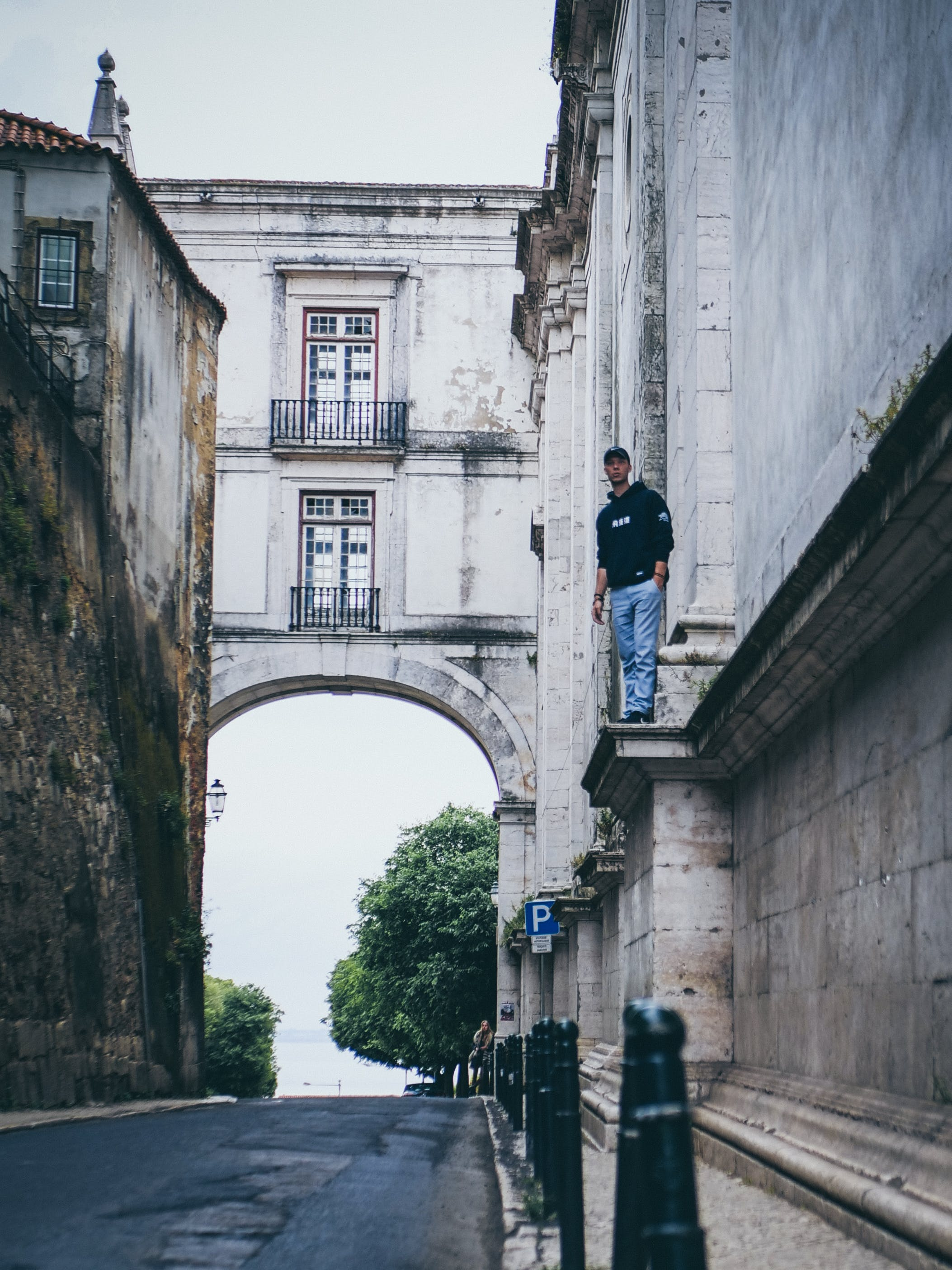 Man Wearing Black Pullover Hoodie Standing on Beside Beige Concrete Building