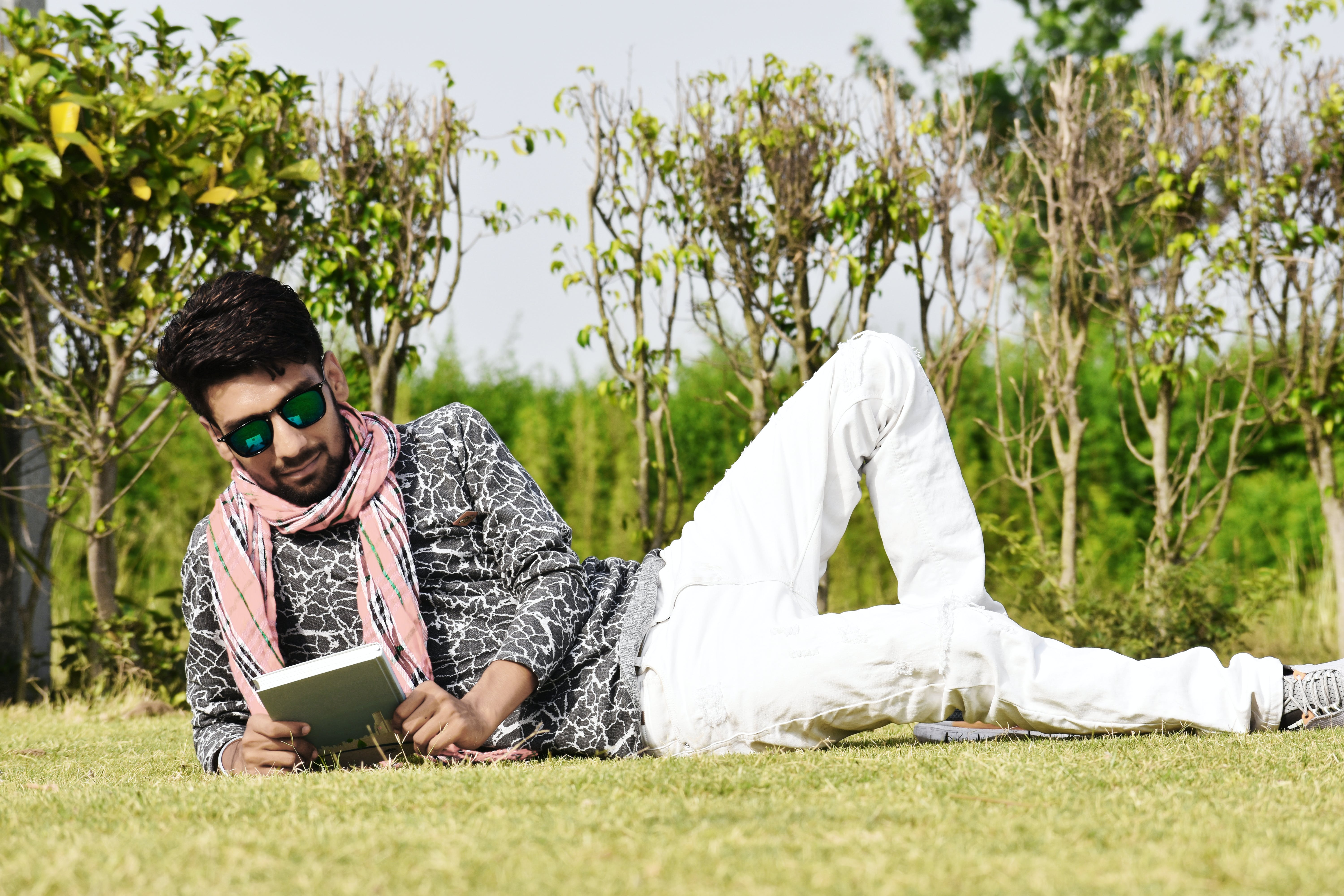 Man in White Pants Wearing Sunglasses Reading Book