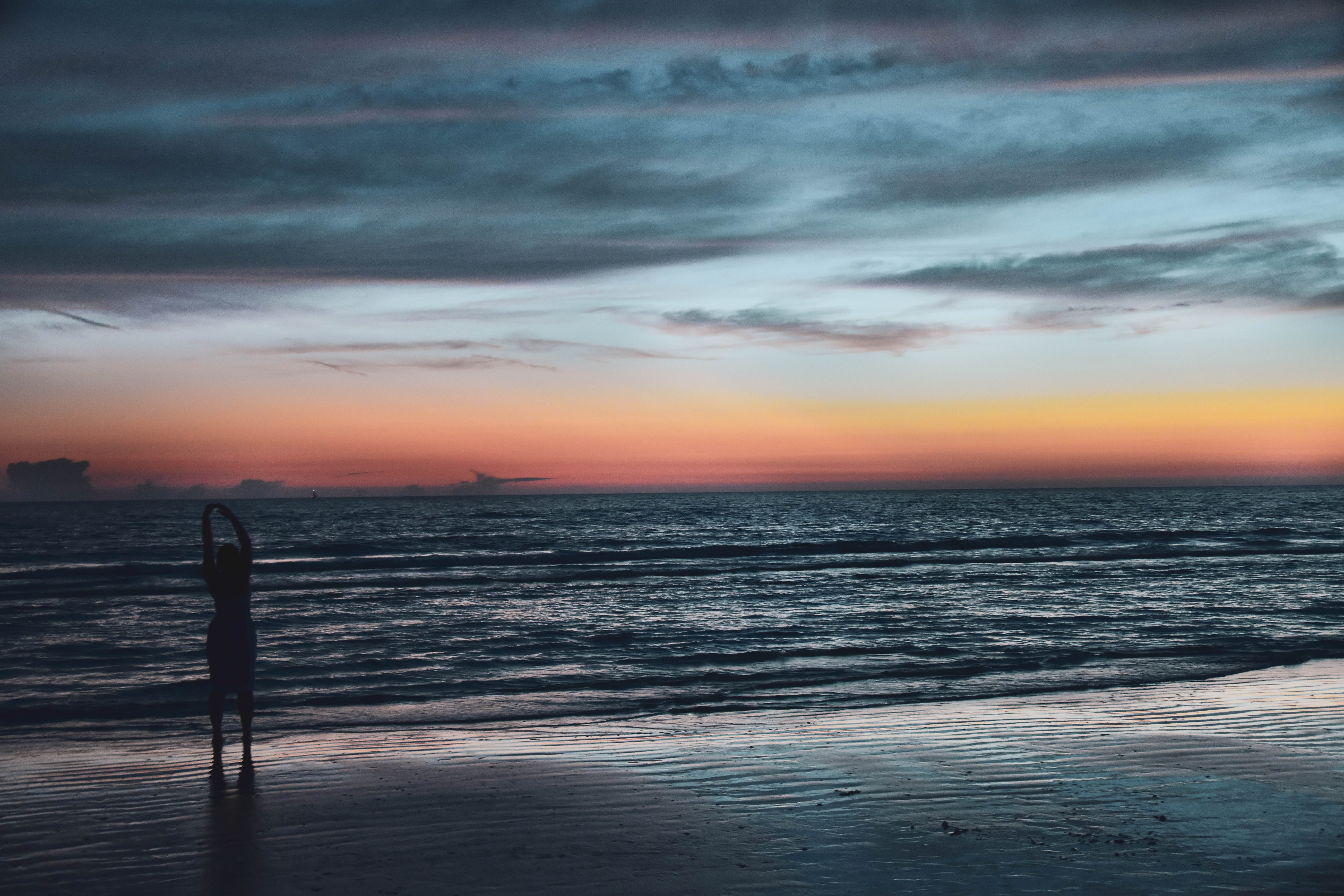 Silhouette of Person on Seashore during Golden Hour