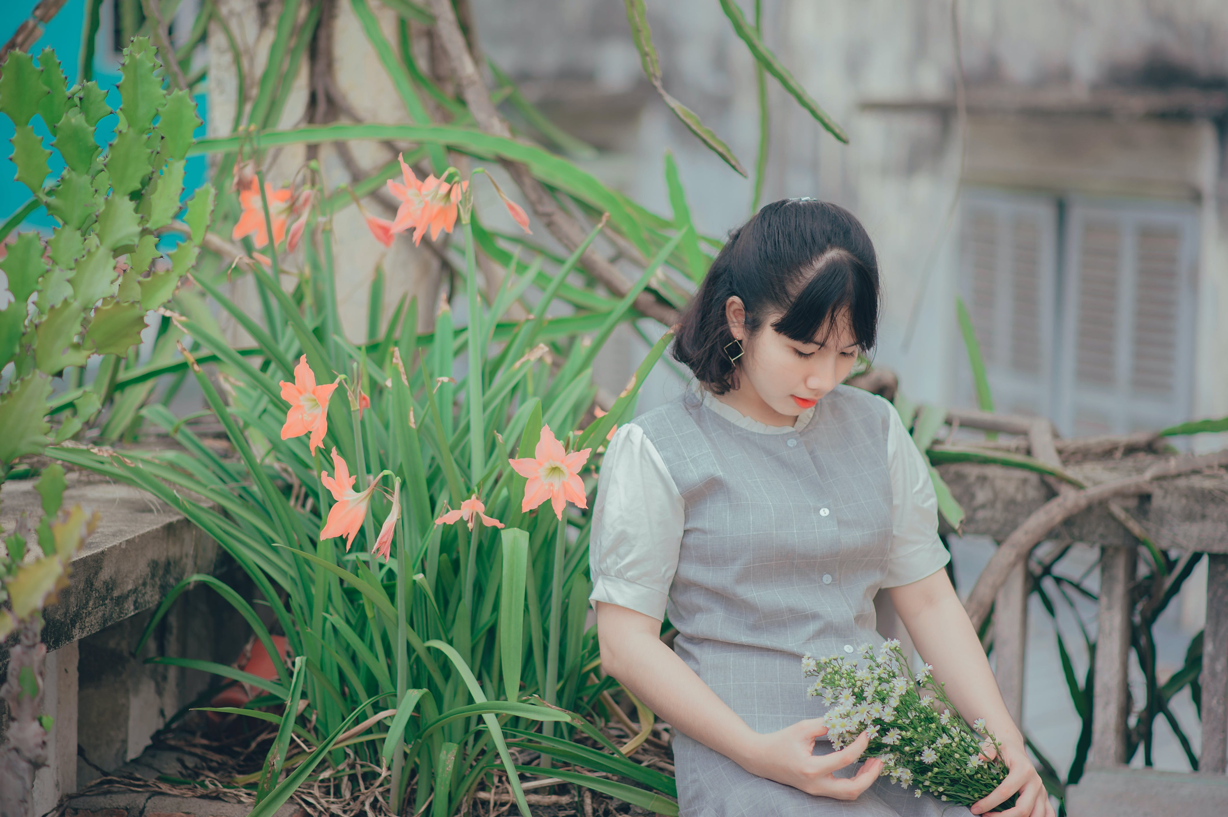 Woman Sitting Beside Pink Petaled Flower While Holding Bouquet of Flower