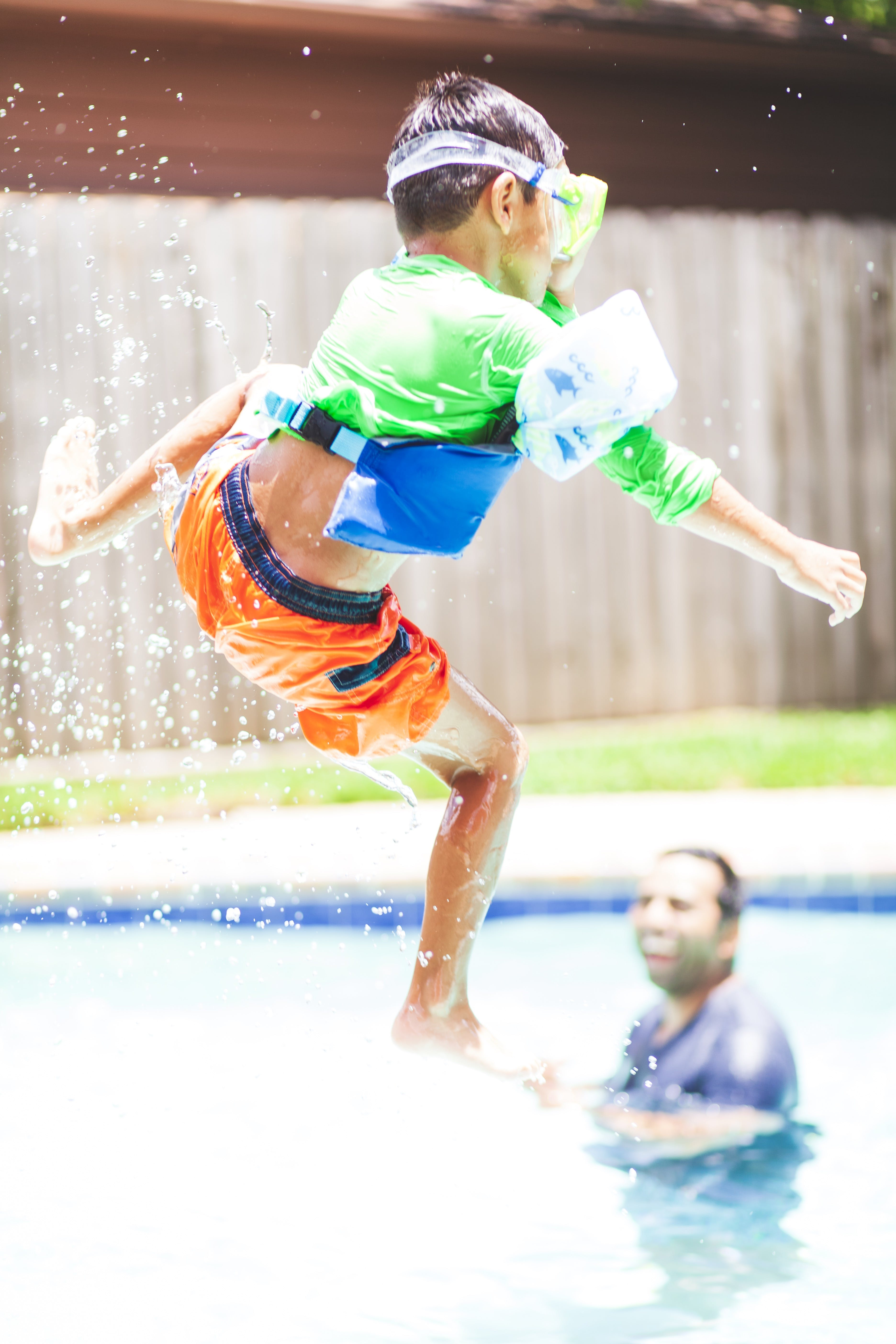 Boy in Green Crew-neck Shirt and Orange Shorts Jump over Swimming Pool