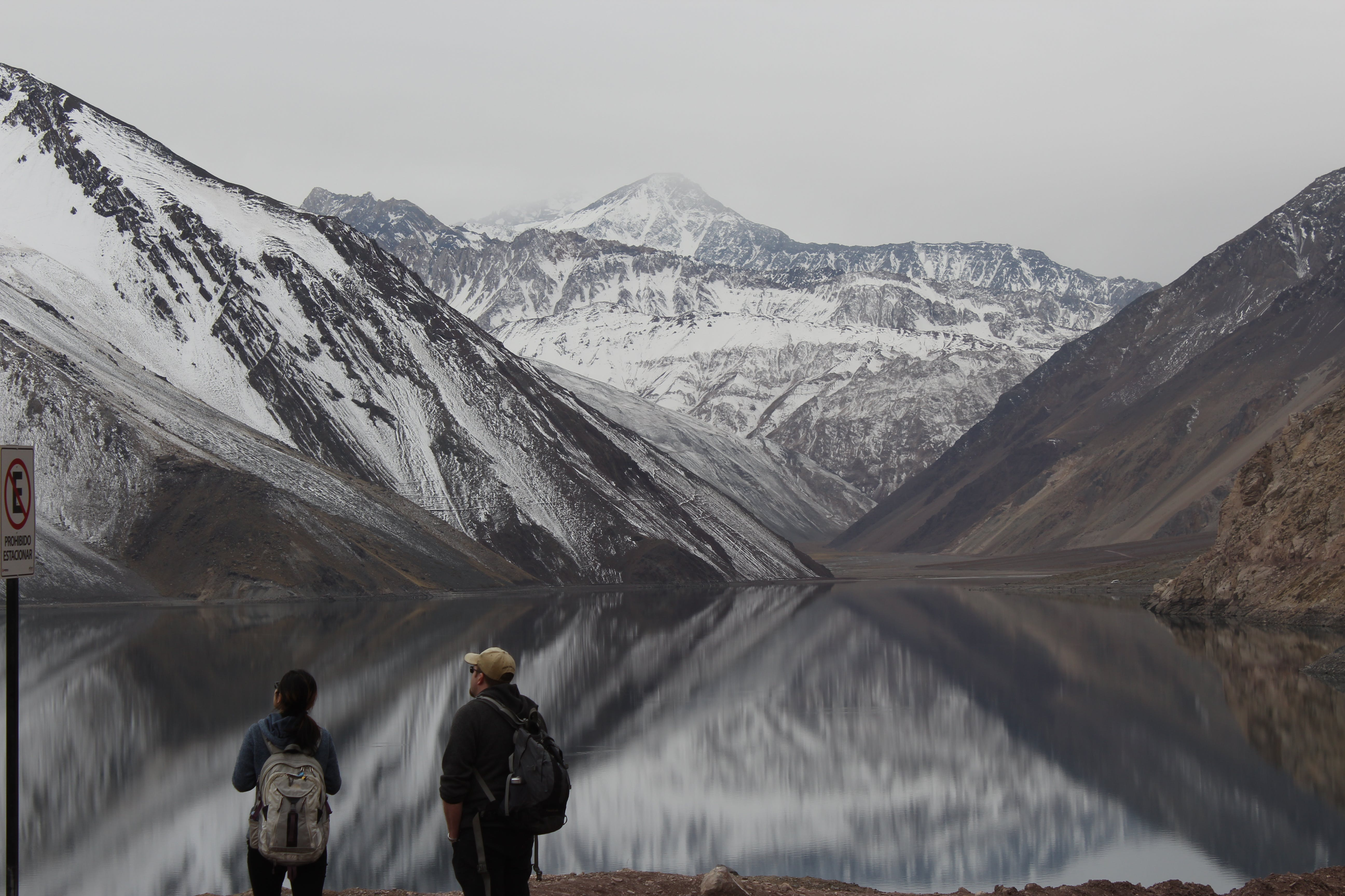 Two Man and Girl Looking at Snow Filled Mountains