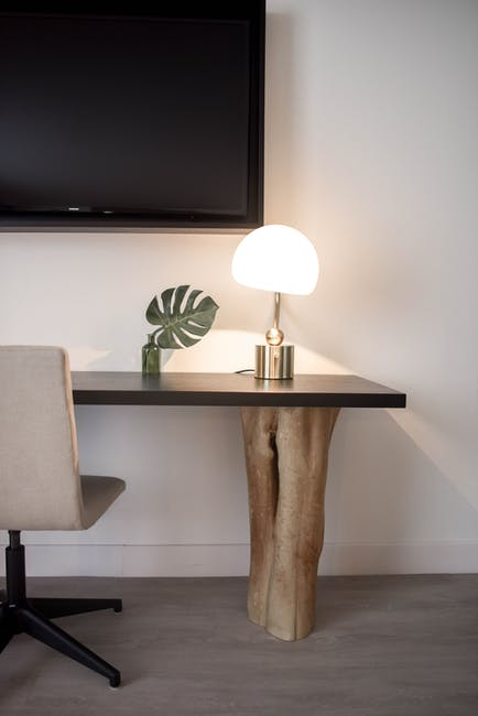Stainless steel base white shade table lamp on brown wooden desk near white painted wall with wall m...