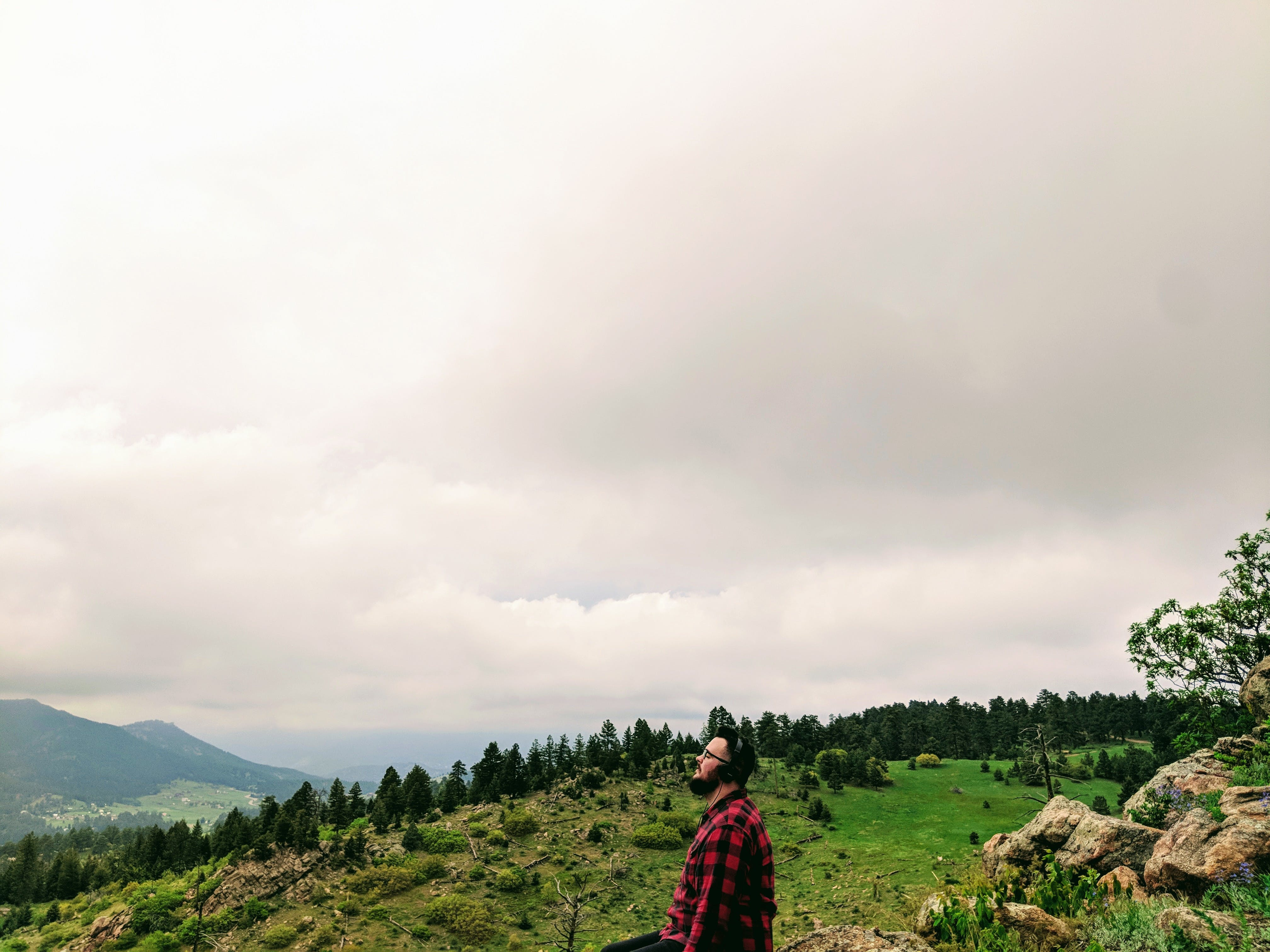 Man Wearing Red and Black Plaid Shirt Standing on Green Grass Hill