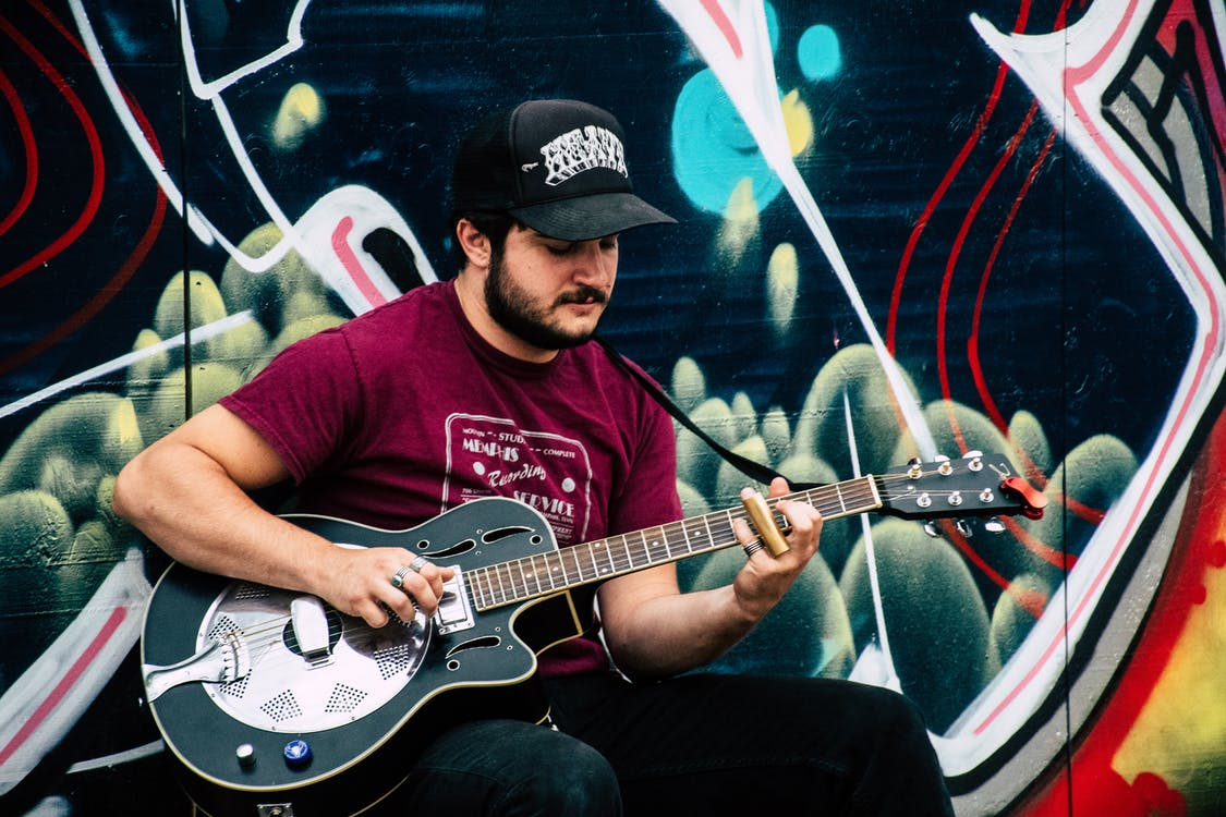 Man in Red Shirt Playing Resonator Guitar Near Wall With Black and Green Painting