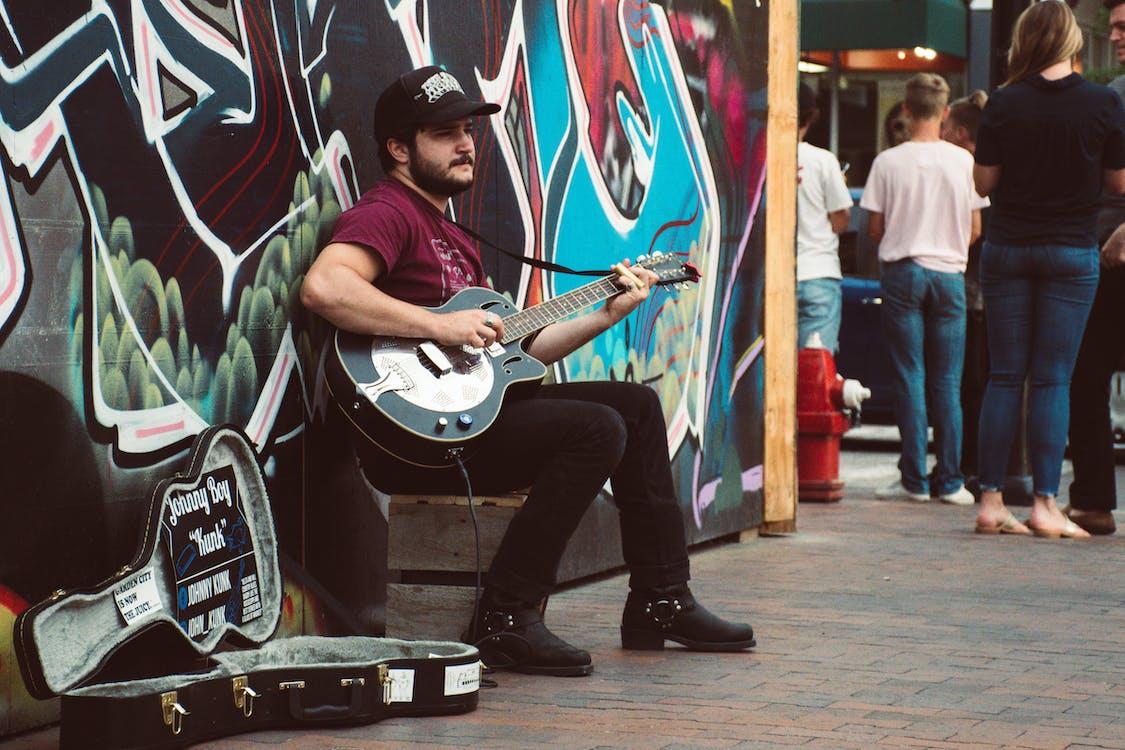 Man Playing Black Cutaway Guitar
