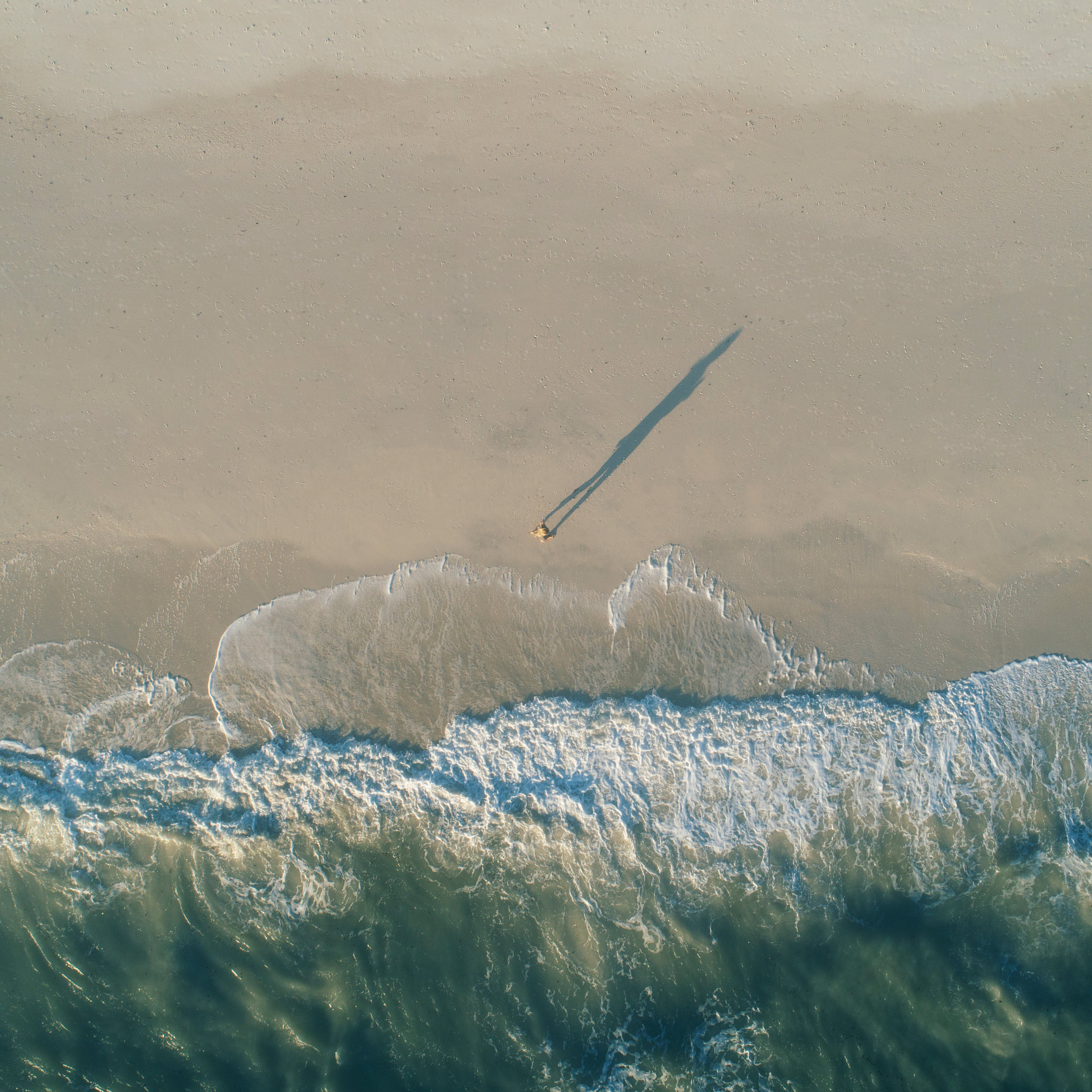 Aerial Photography of Person Walking on Beach