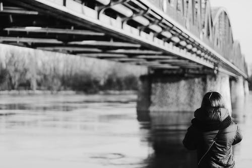 Grayscale Photo Of Person Wearing Jacket Near Bridge