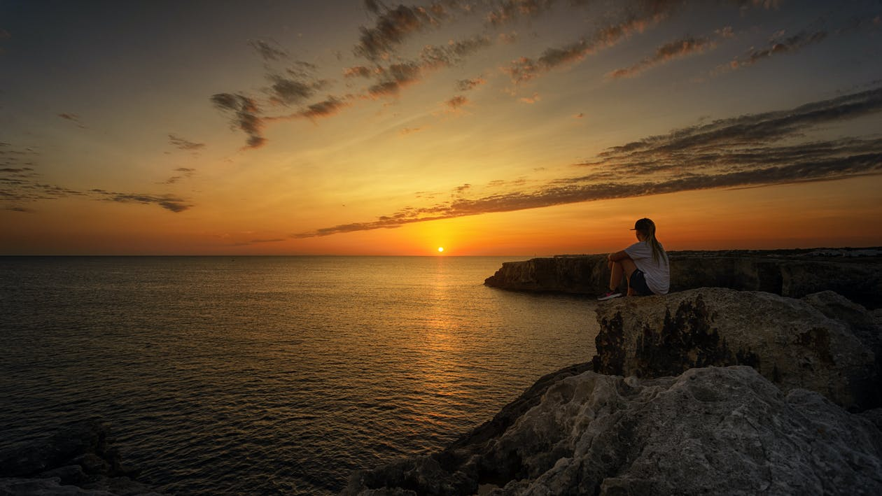 Photo of Person Sitting on Rock During Sunset