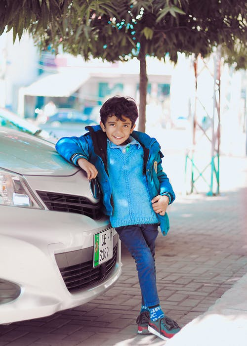 Photo of a Boy Leaning on Car