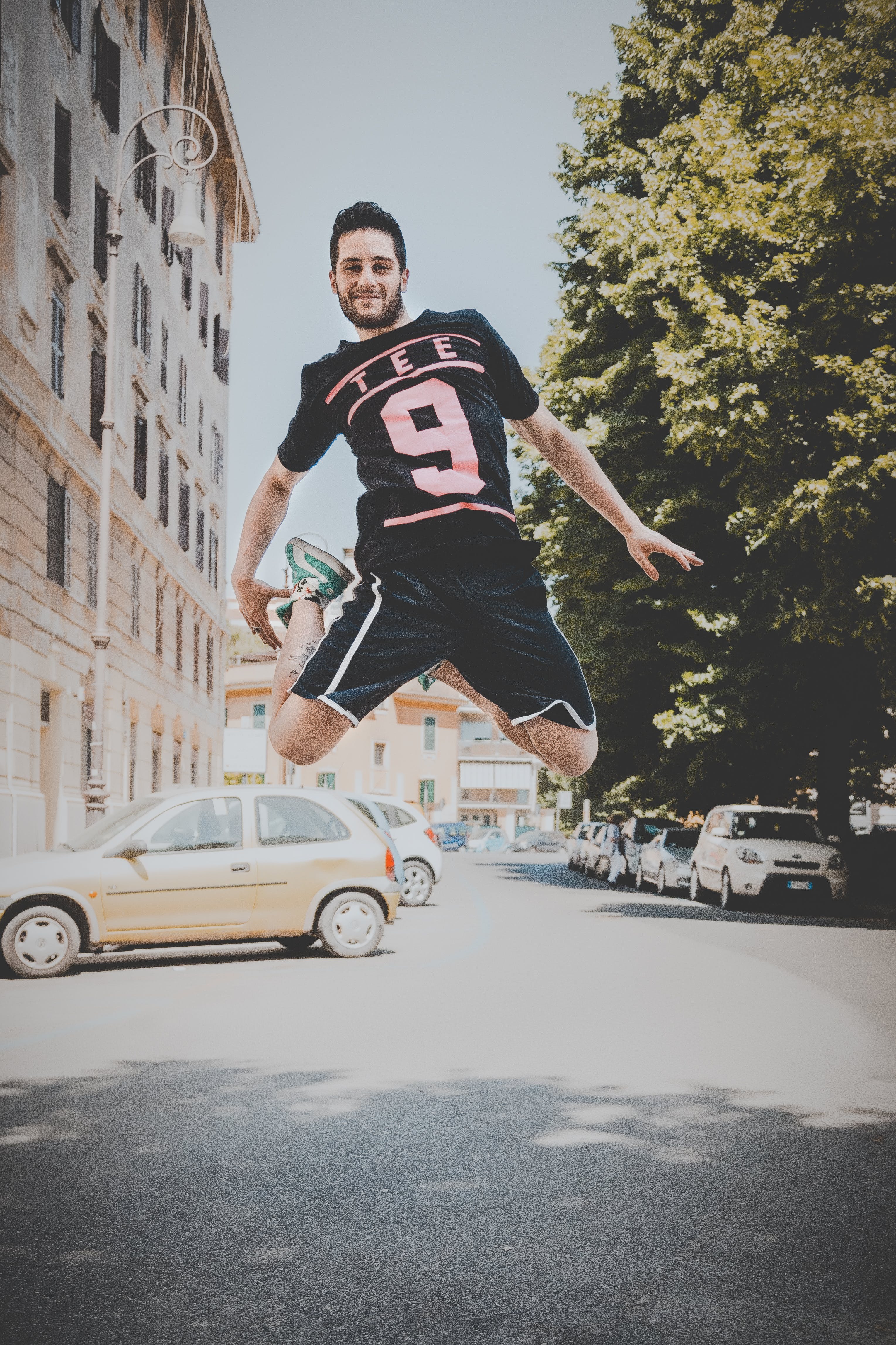Photo of a Guy Jumping on Road