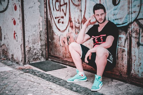 Man In Black T-shirt And Shorts Leaning on Wall