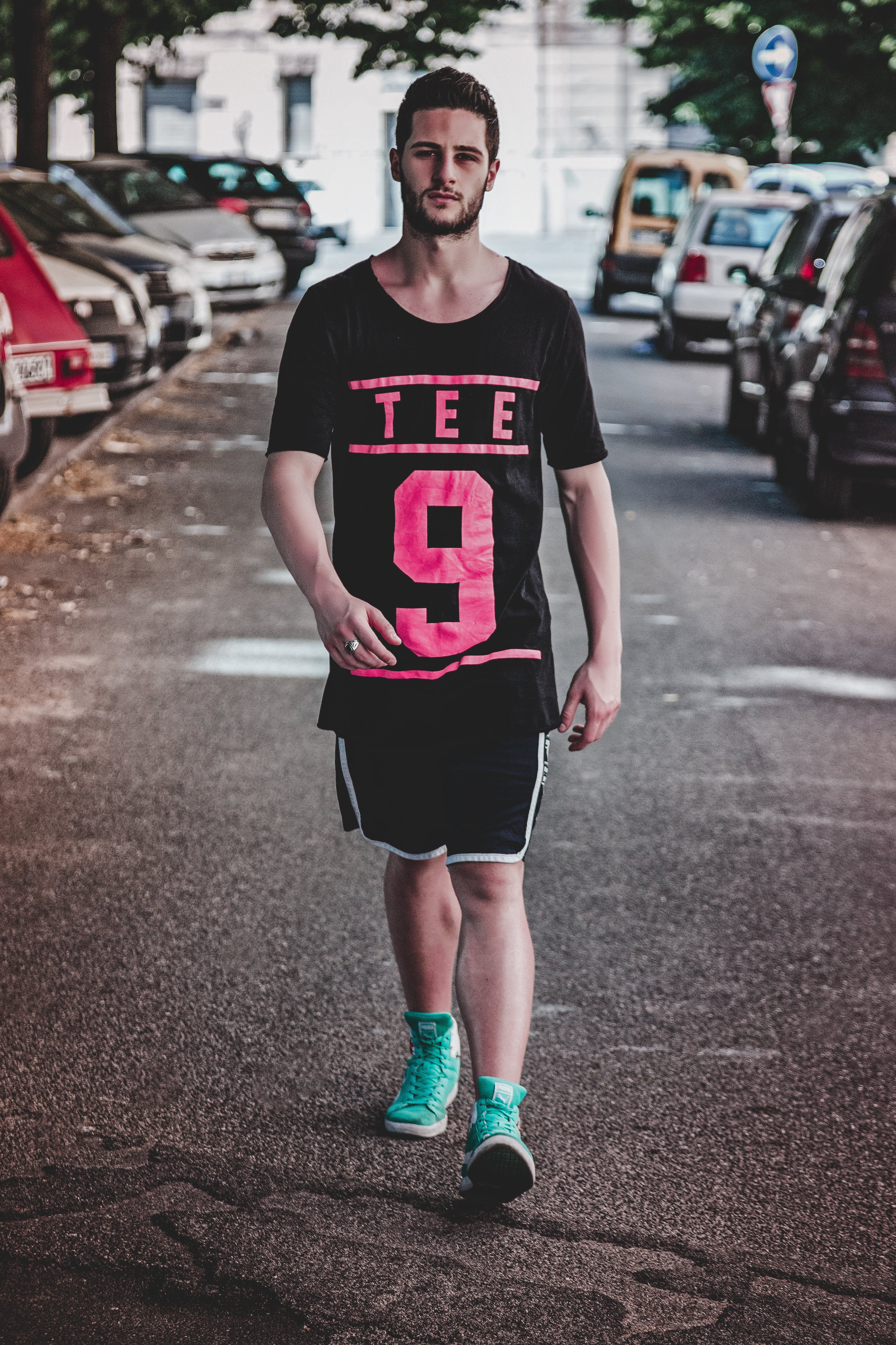 Man Wearing Black Crew-neck T-shirt, Black Shorts, and Pair of Teal High-top Sneakers Walking Between Vehicles