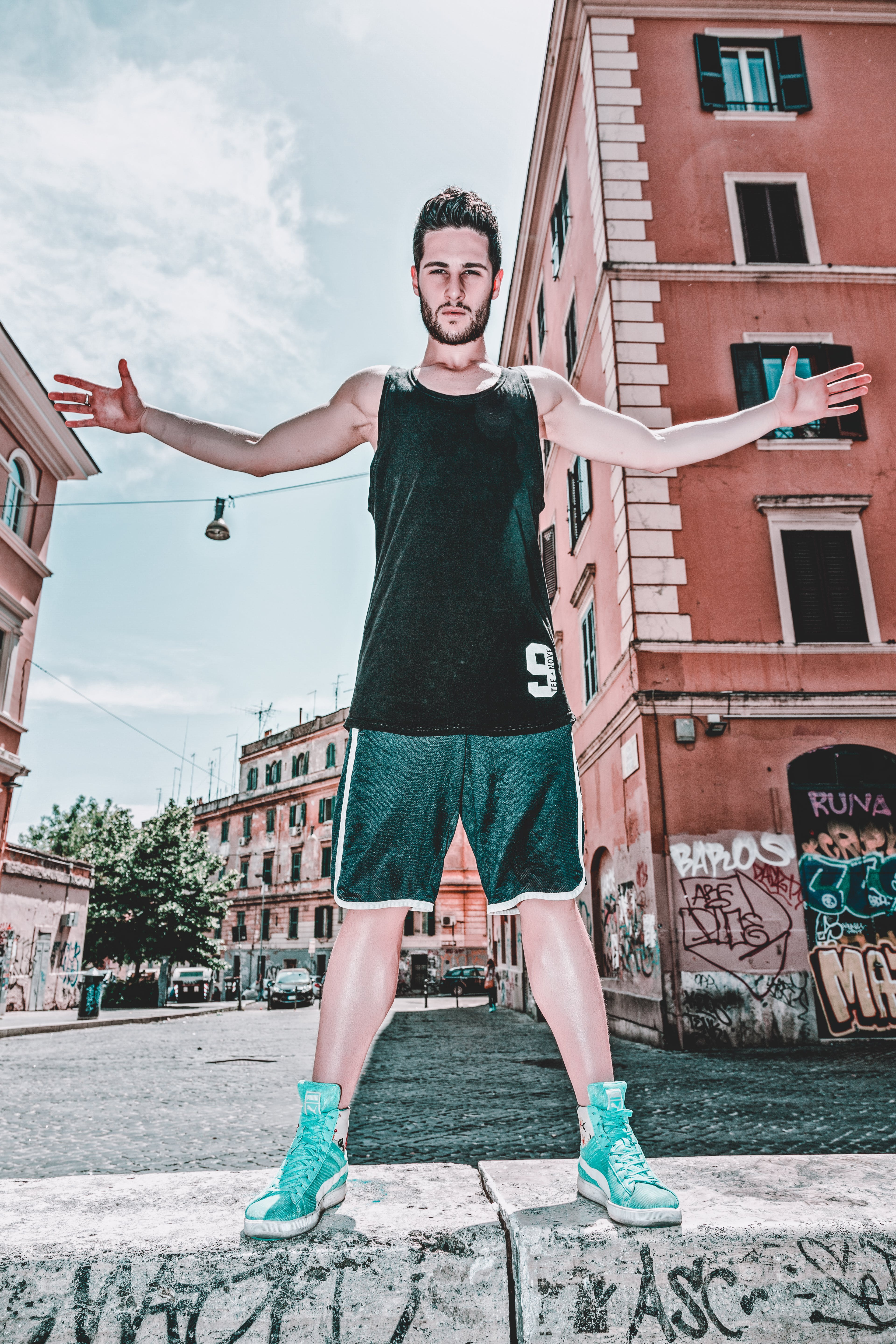Man In Black Tank Top And Green Shorts Posing Near Building