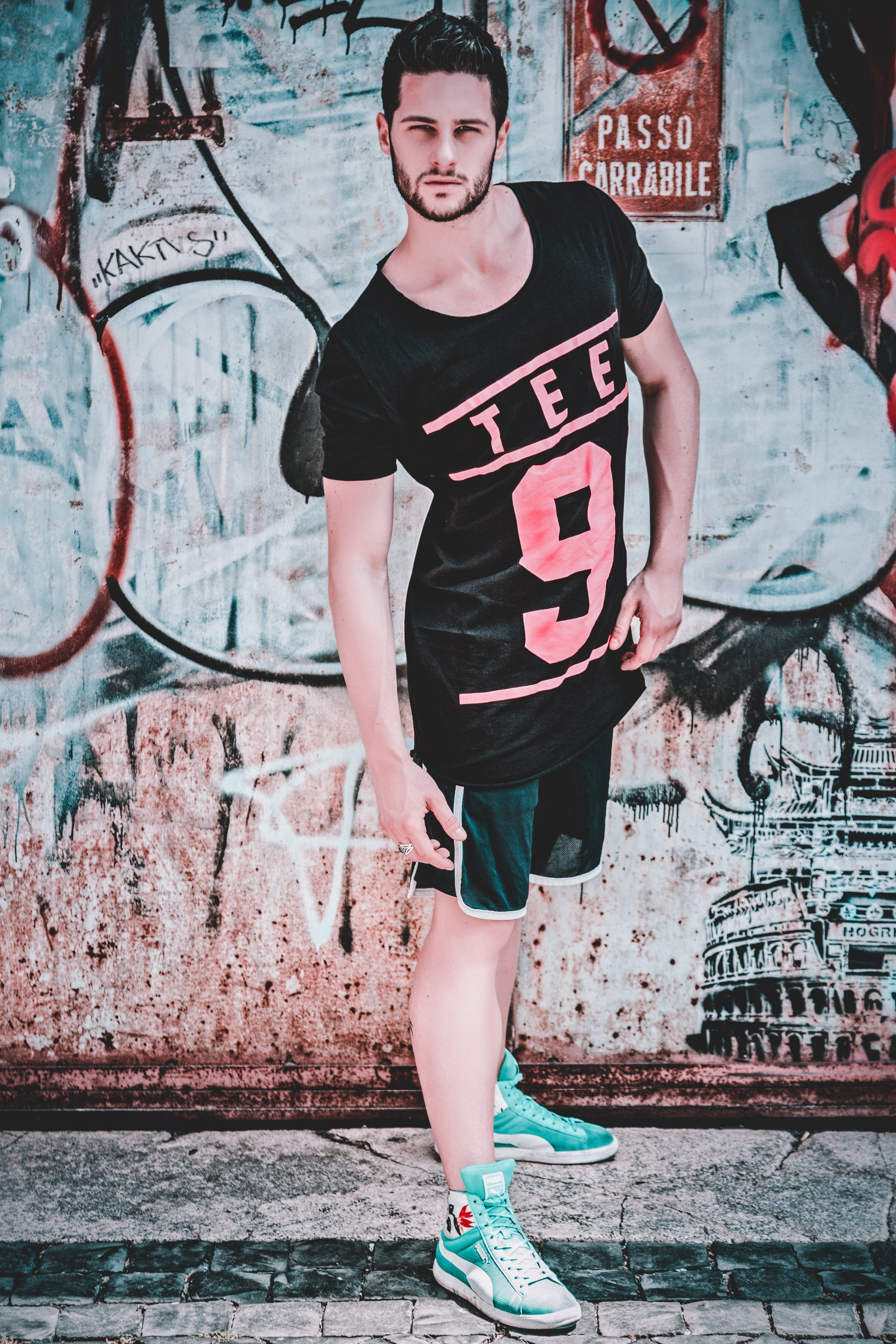 Man Wearing Black and Pink Tee 9-printed T-shirt in Front of Wall