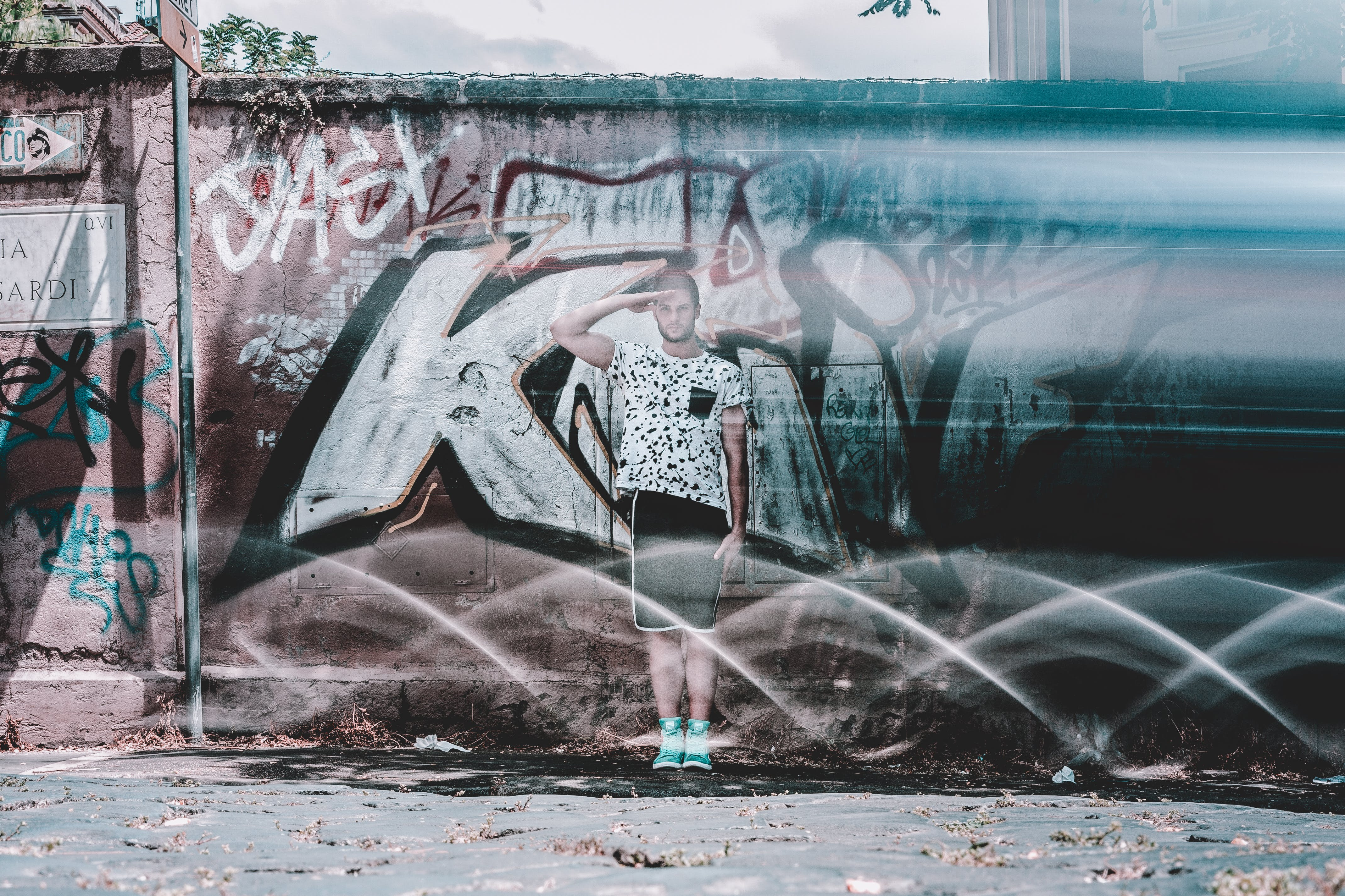 Man in White Shirt and Black Shorts Saluting Graffiti at Daytime