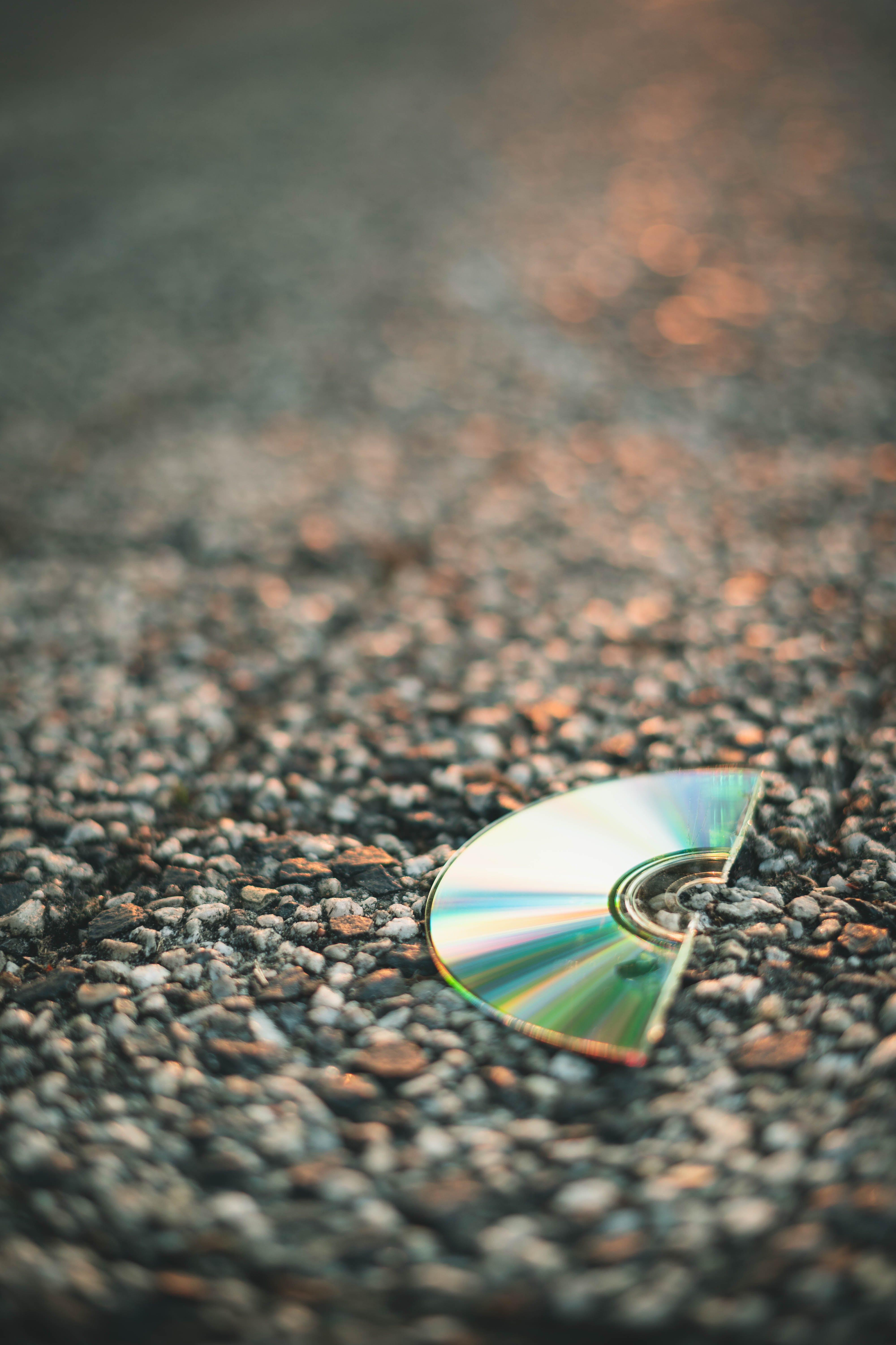 Selective Focus Photography of Half Cut Compact Disc on Gray Pavement