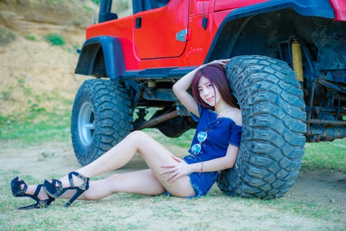 Woman Wearing Blue Off-shoulder Blouse and Blue Denim Short Shorts Sitting Near Red Truck
