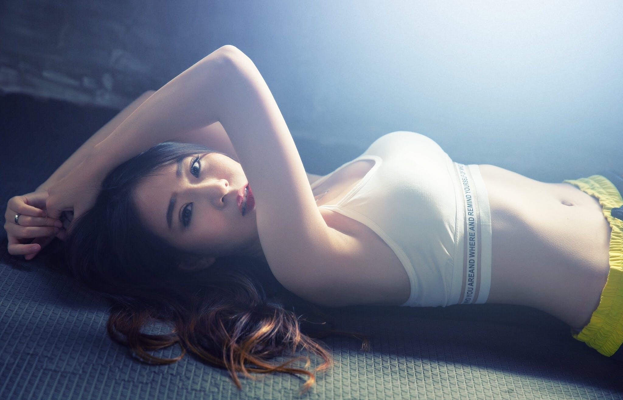 Woman Wearing White Sport Bra Lying on Black Mat