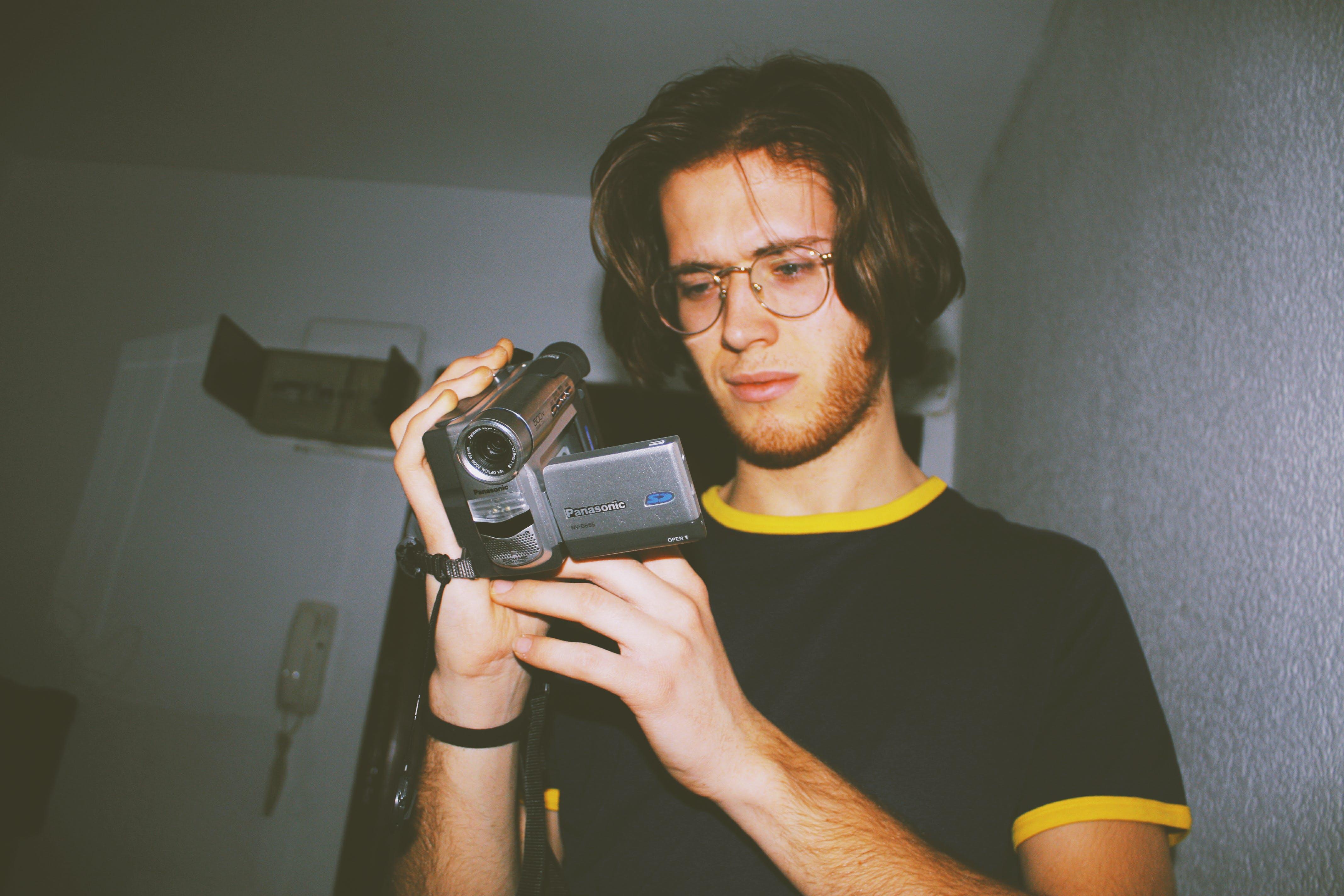 Man Wearing Black Shirt Holding Digital Camcorder