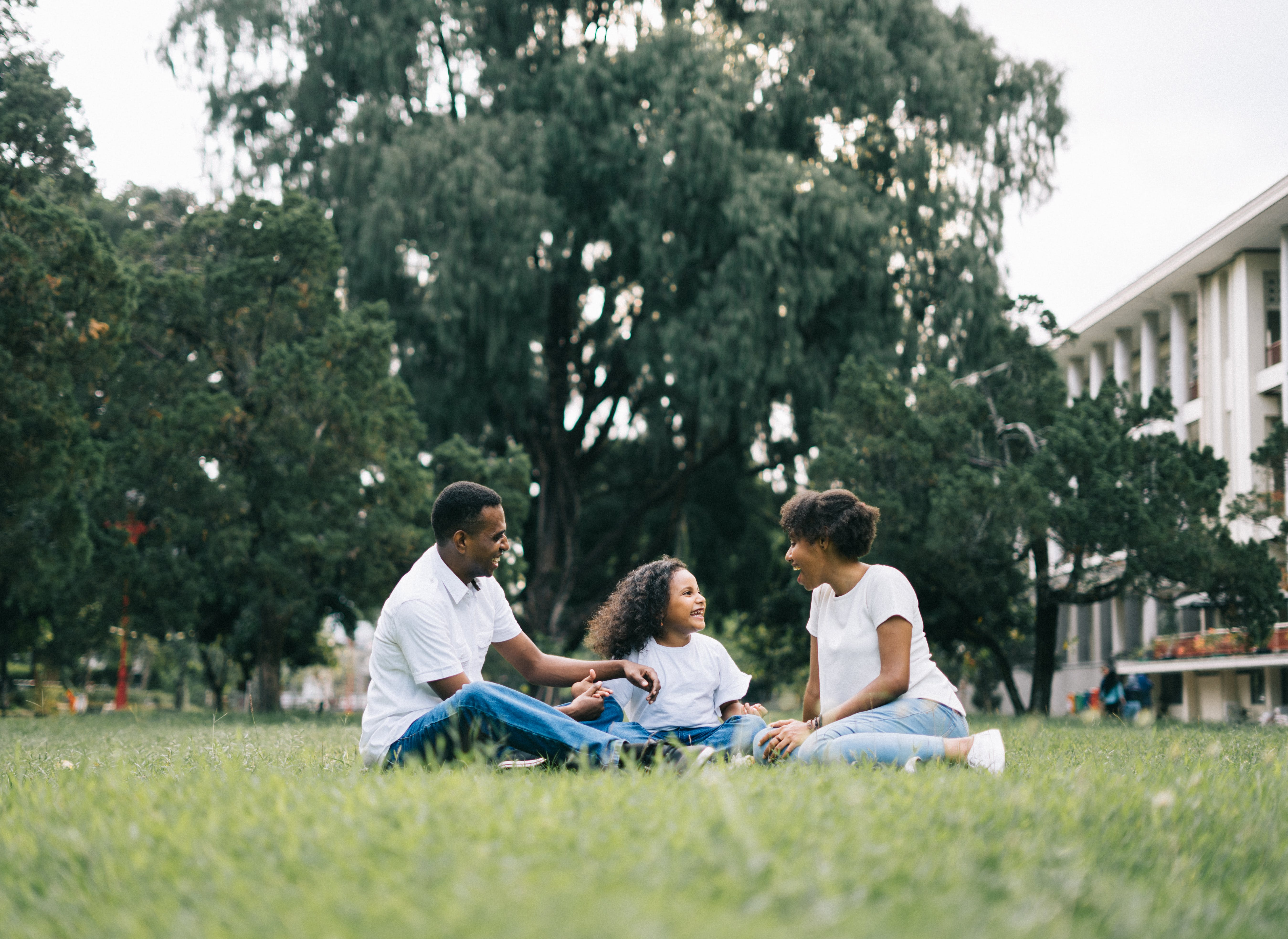 Family Sitting on Grass Near Building