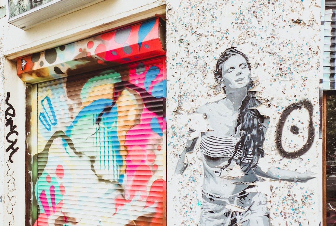 Stencil Art of Woman on Wall Near Door Shutter With Graffiti