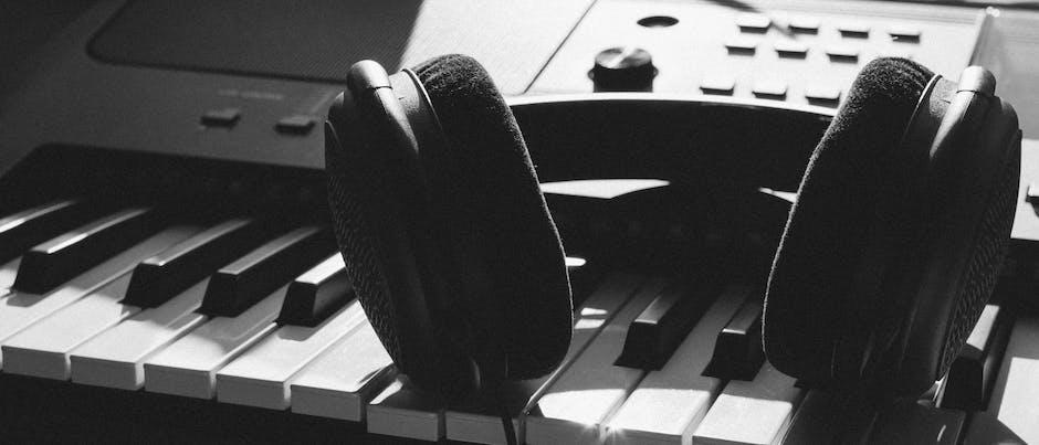 Black wireless headphones on gray electronic keyboard