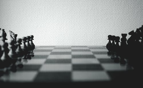 Black and White Chessboard Set Near White Wall