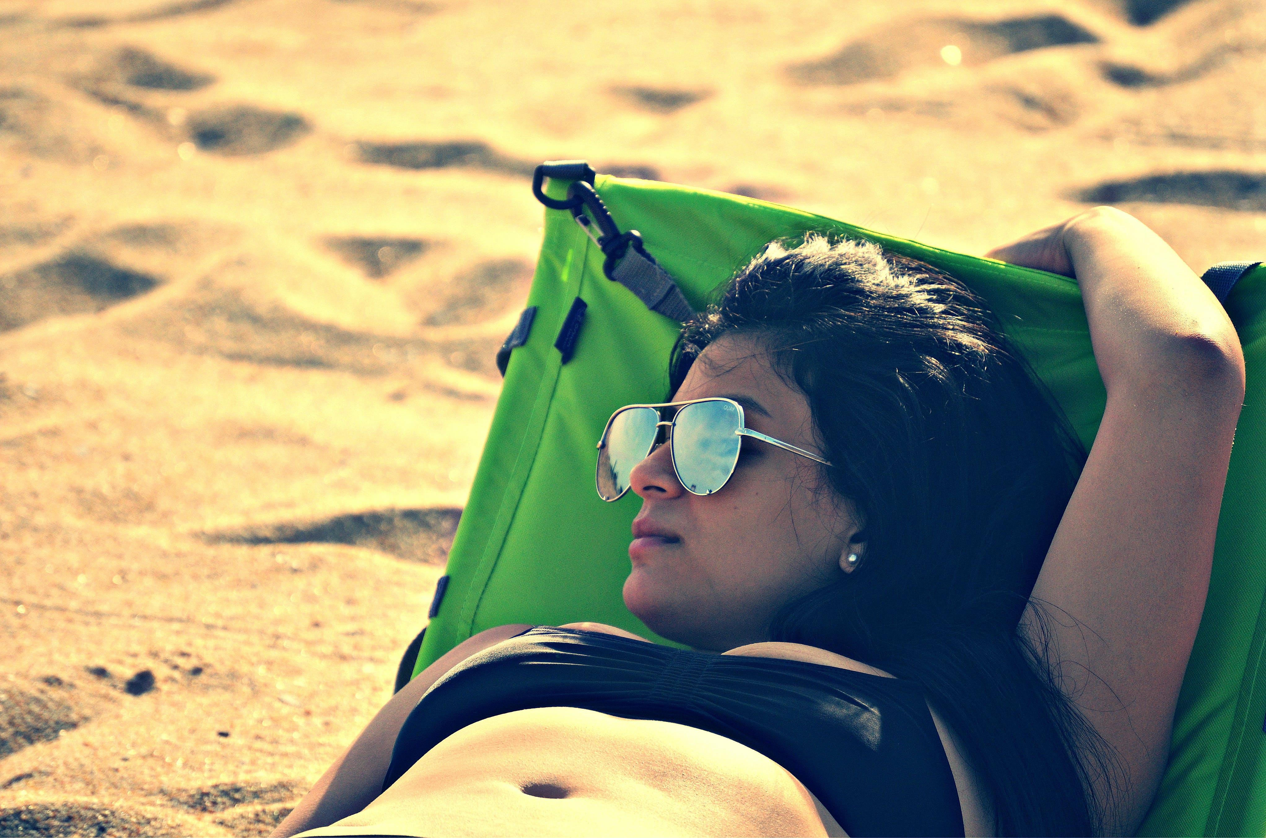 Woman Wearing Bikini Top Lying on Bed Beside Sand at Daytime