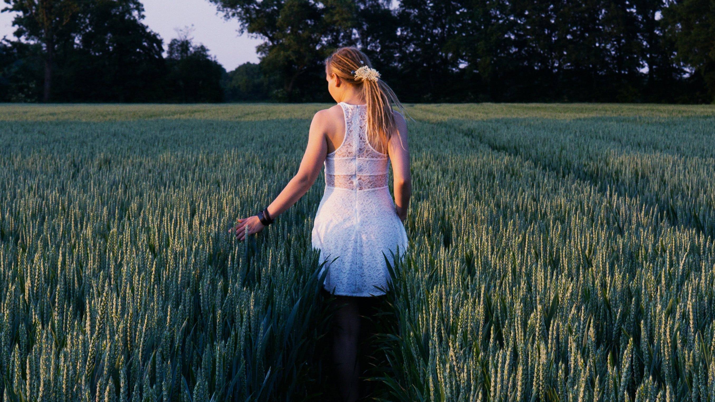 Woman Walking in Between Grass Field at Daytime
