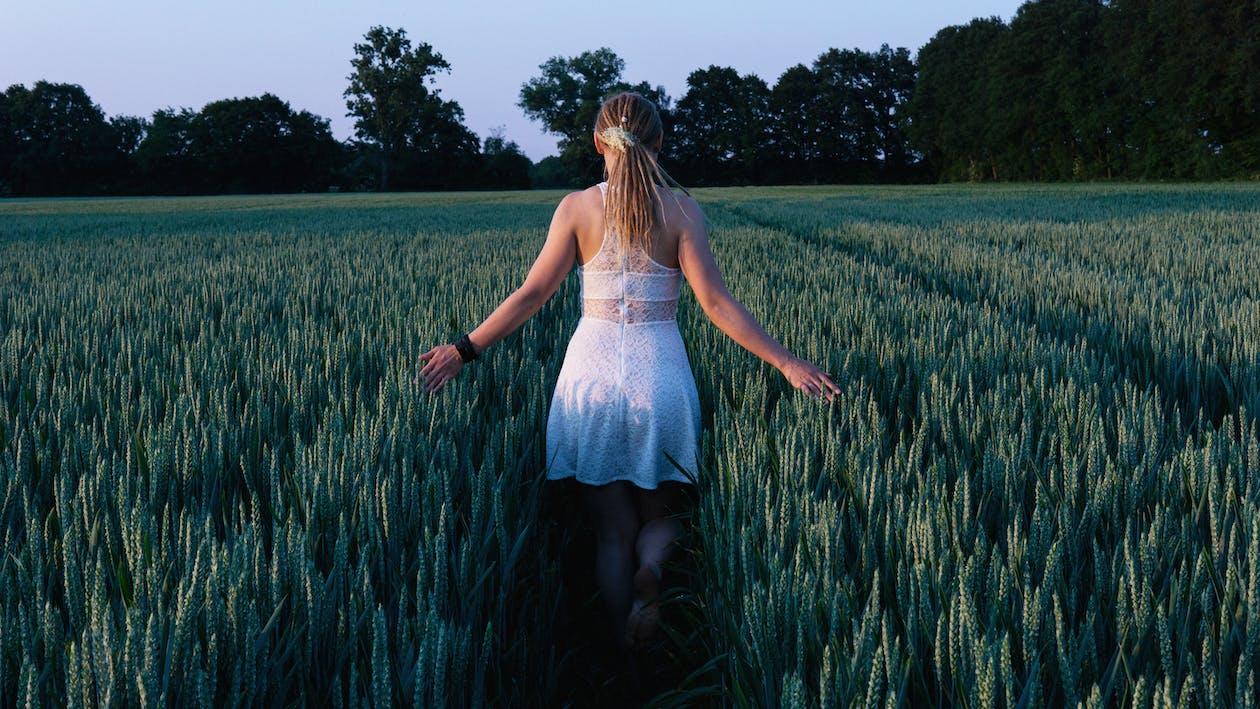 Woman in White Sleeveless Mini Dress Standing Between Grass Field