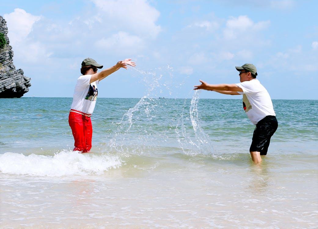 Man And Woman Splashing Water To Each Other