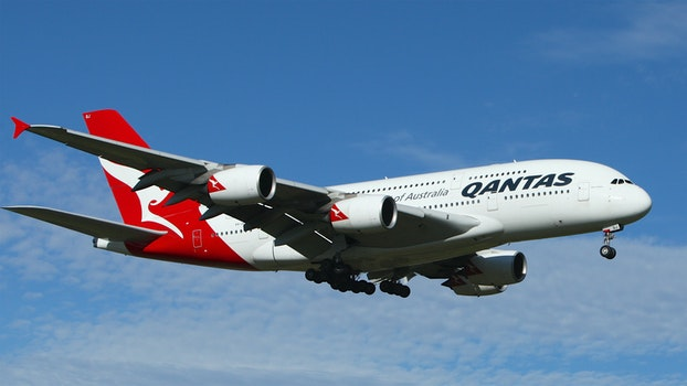 White and Red Qantas Airplane Fly High Under Blue and White Clouds