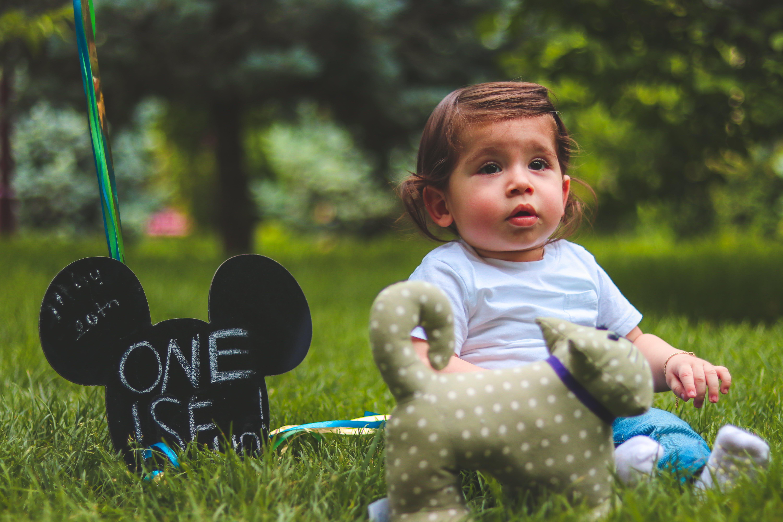 Baby Sitting on Green Grass Field