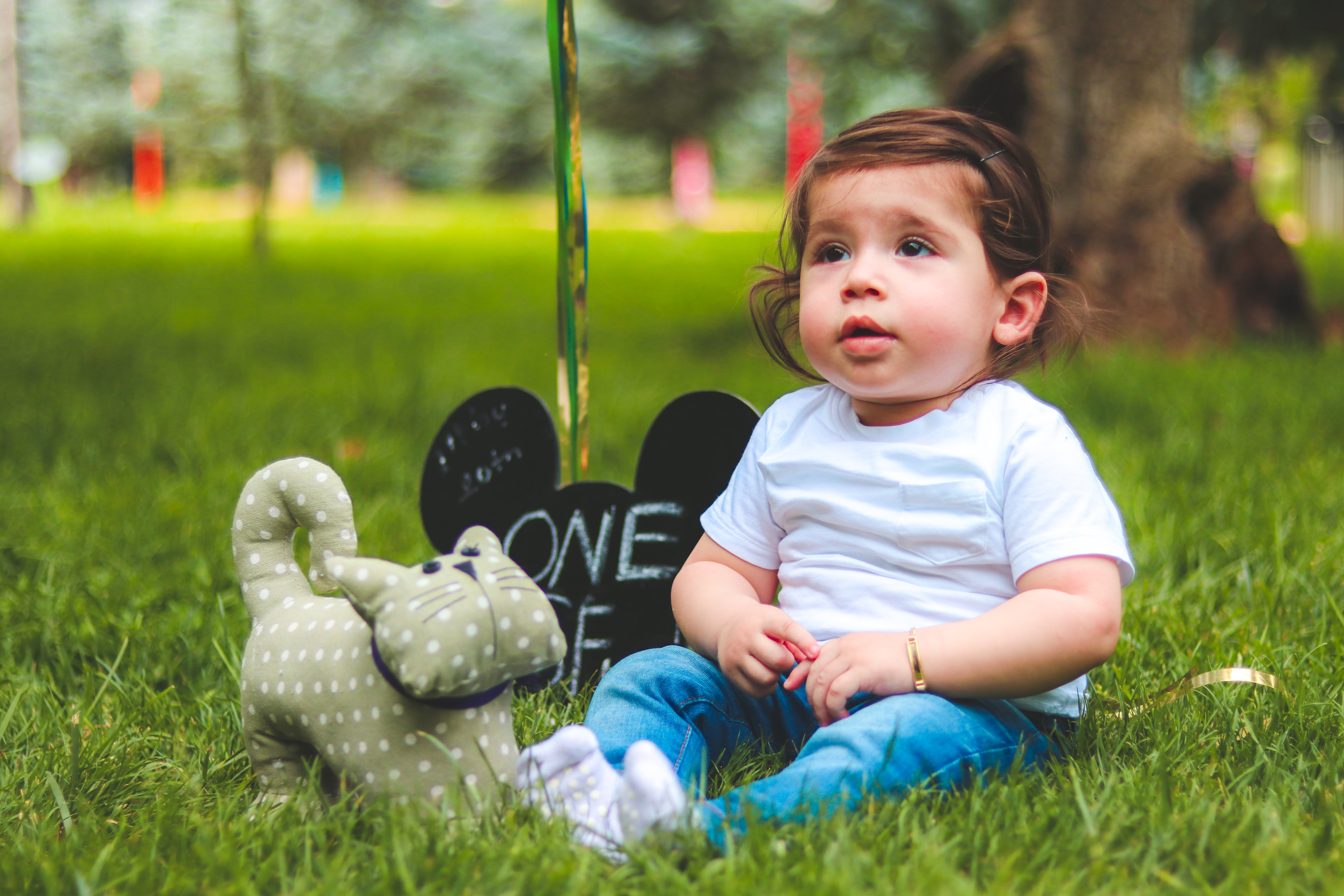 Depth of Field Photography of Baby Sitting on Green Grass
