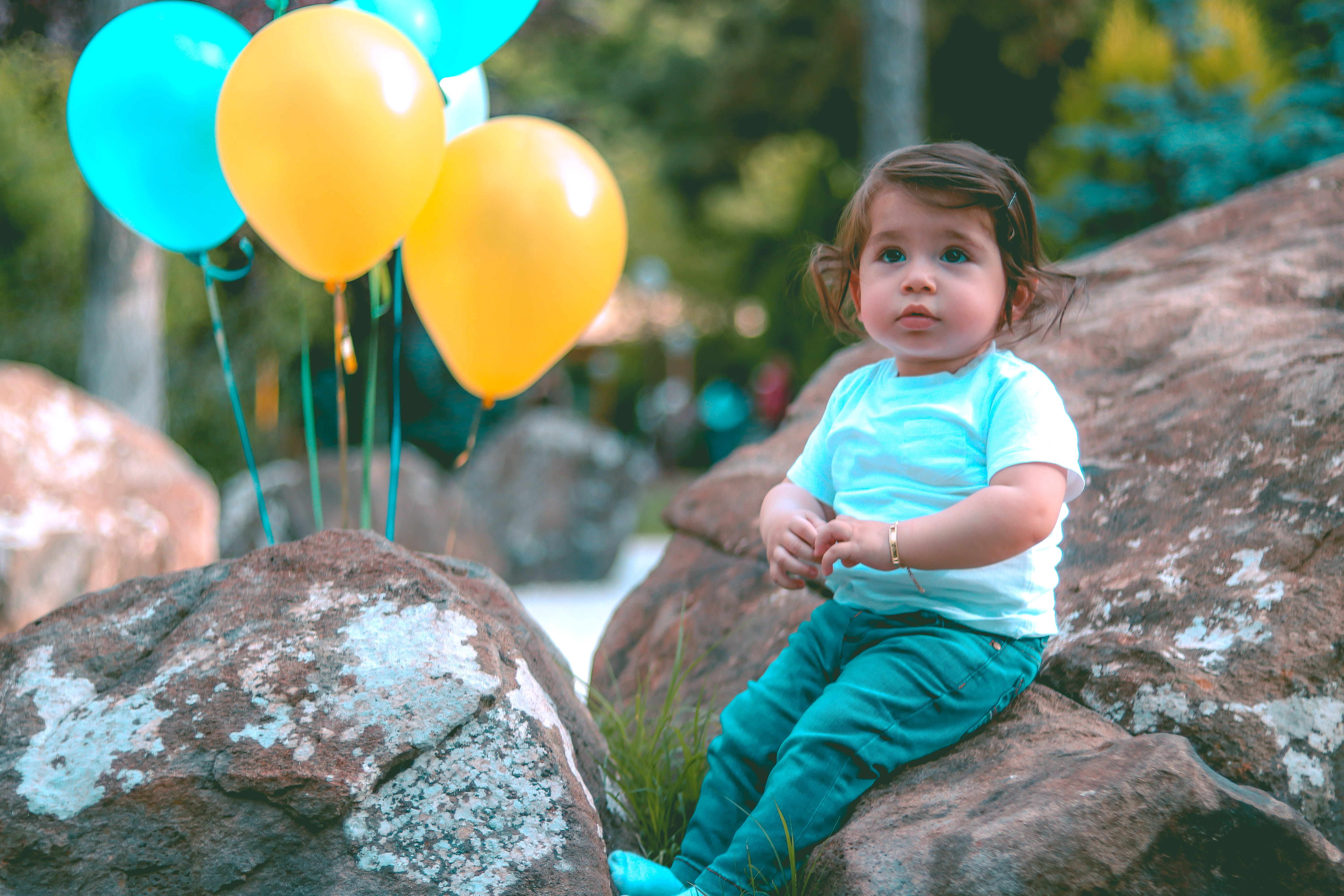 Toddler Wearing White Shirt Sitting on Rock Beside Yellow and Blue Balloons