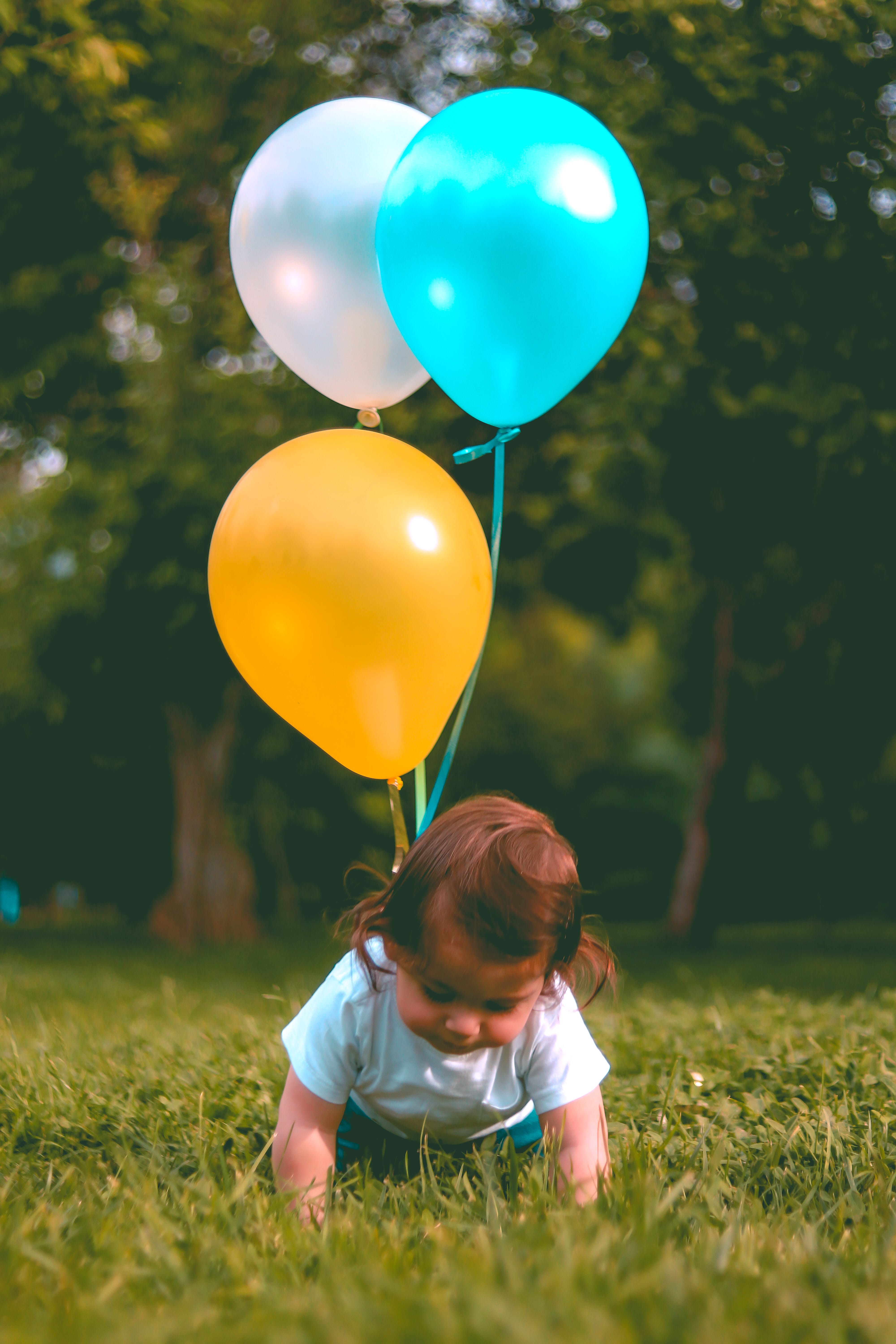 Baby Wearing White T-shirt Holding Three Yellow, Blue, and White Balloons on Green Grass Near Woods