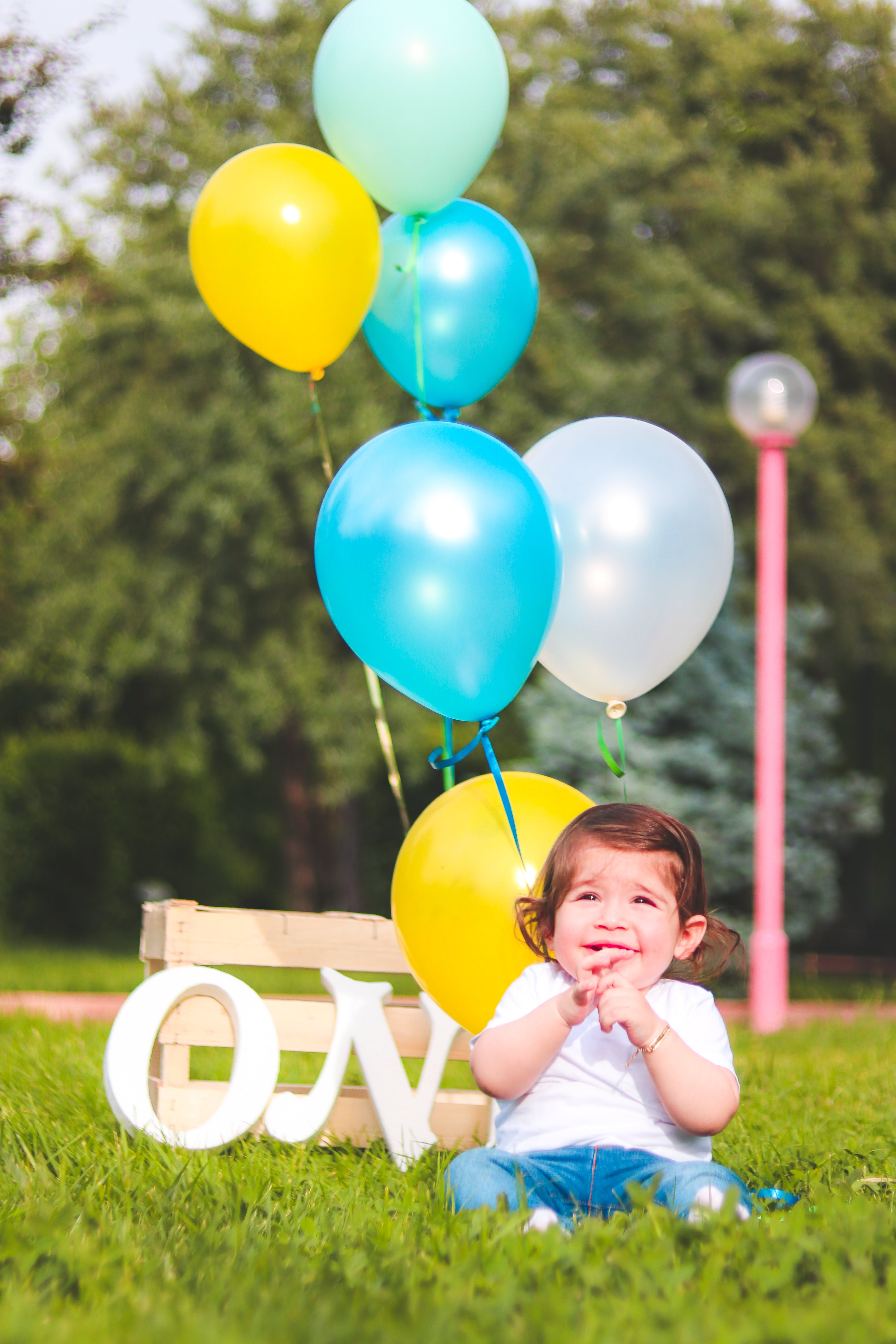 Girl Wearing White Shirt Near Teal, White, and Yellow Ballons