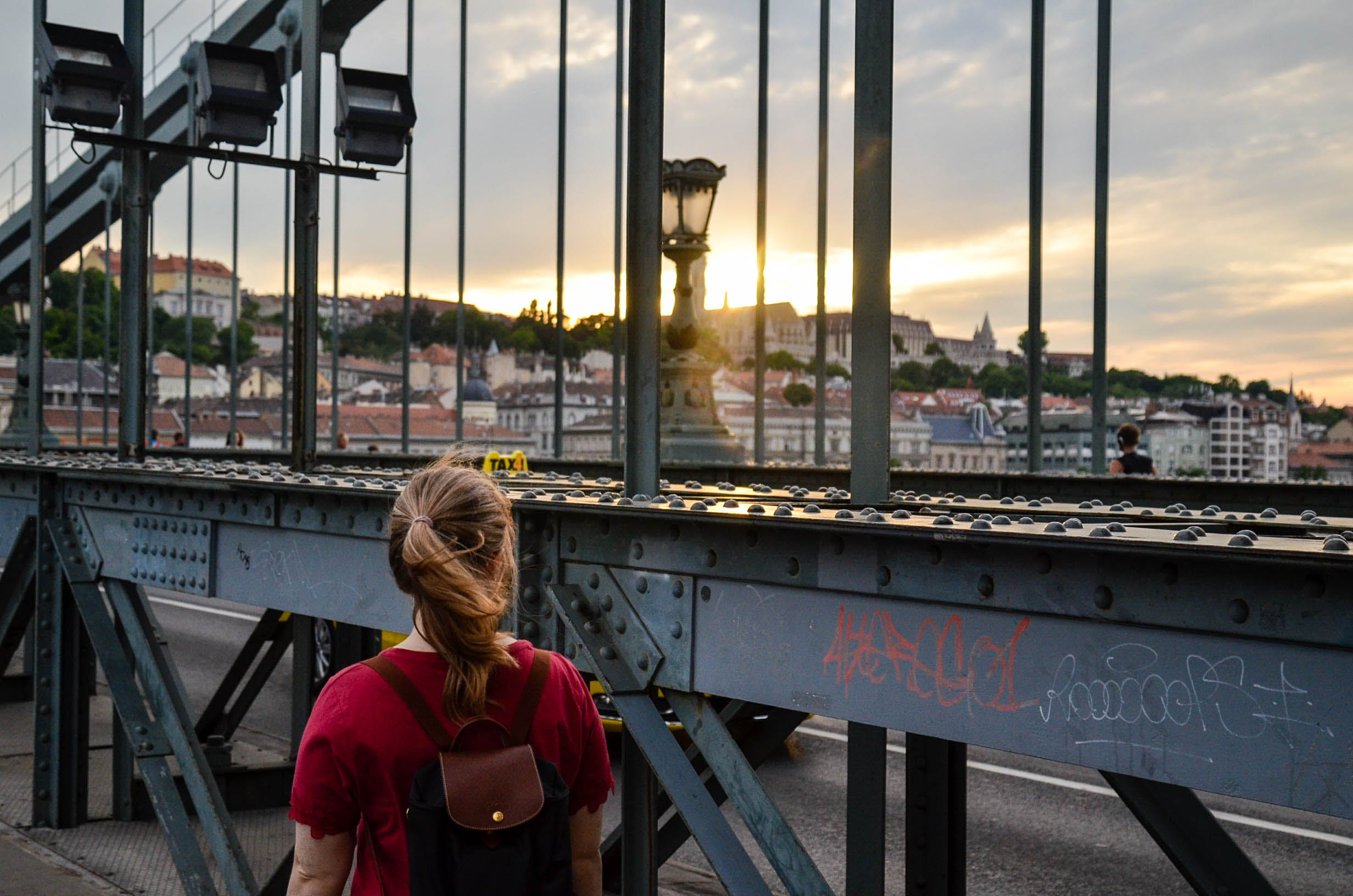 Woman Standing Facing a Bridge
